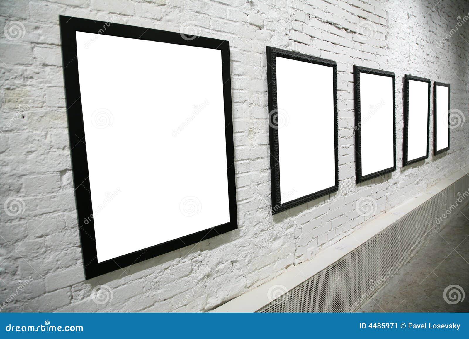 row of black frames on white brick wall