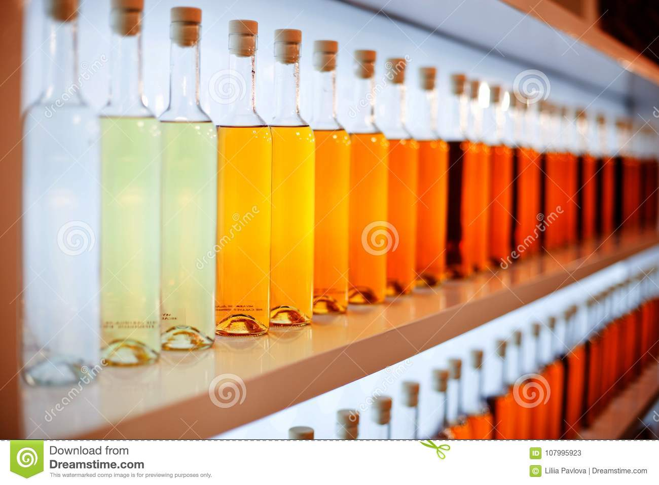 A row of colored bottles with cognac