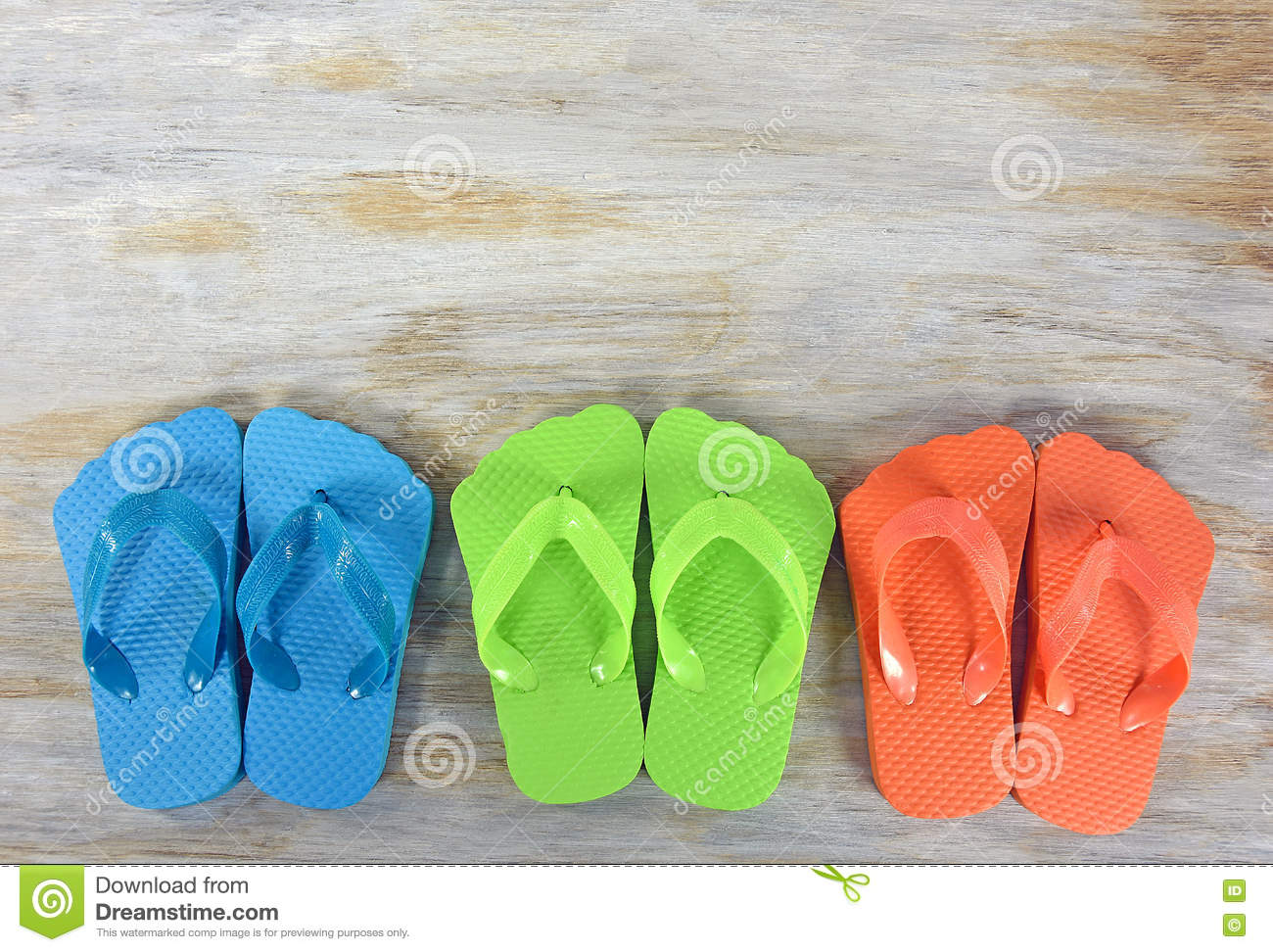 Row of colorful flip-flops on wood