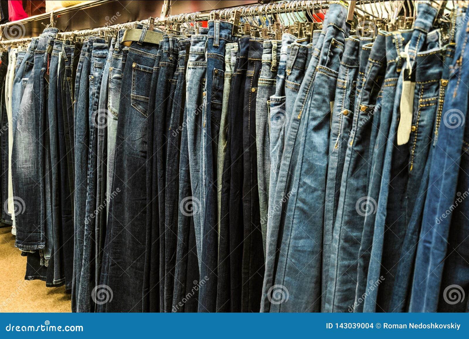 Row of denim pants hanging on trempels