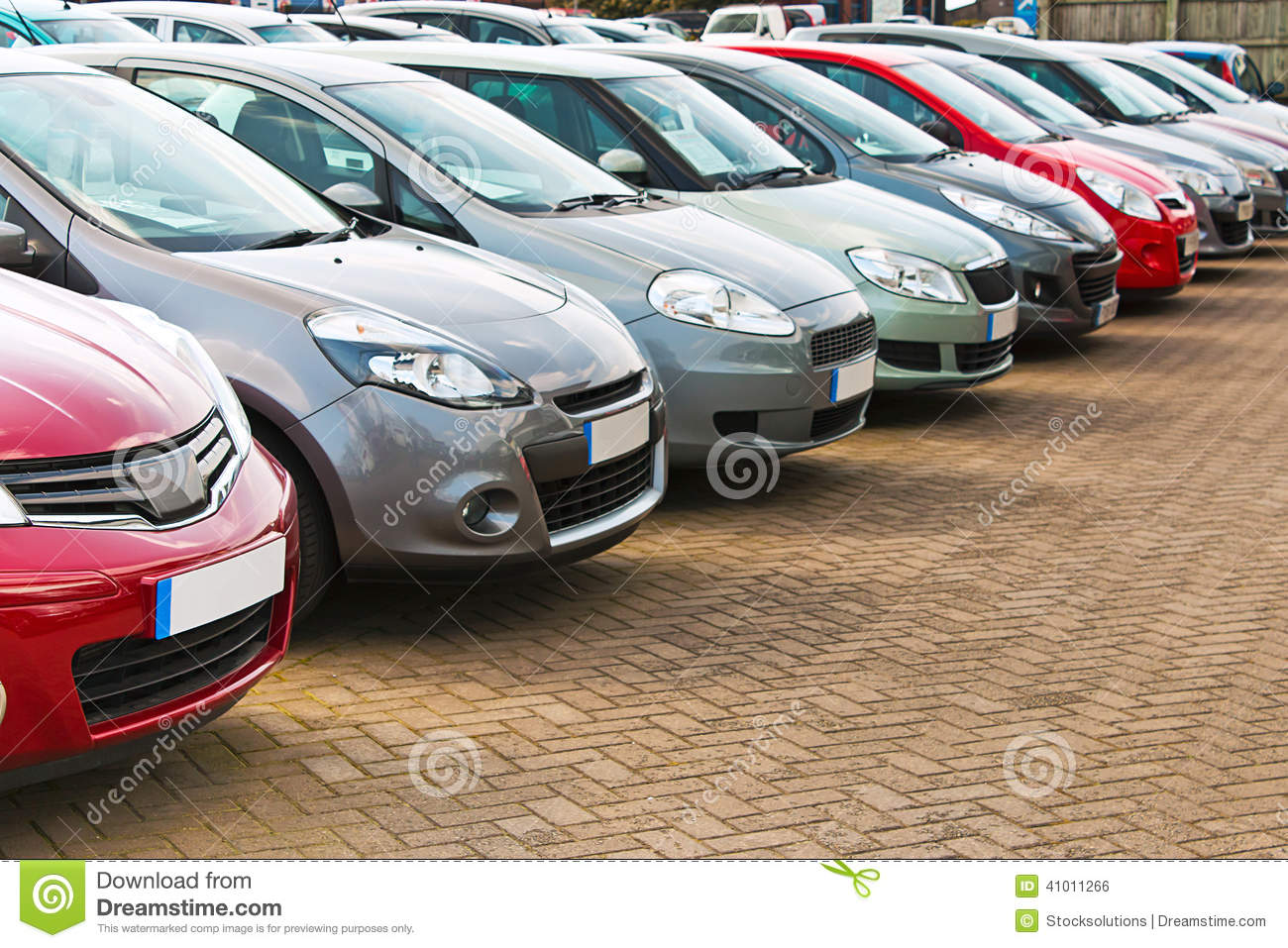 line up of various types of used cars for sale on a motor dealers
