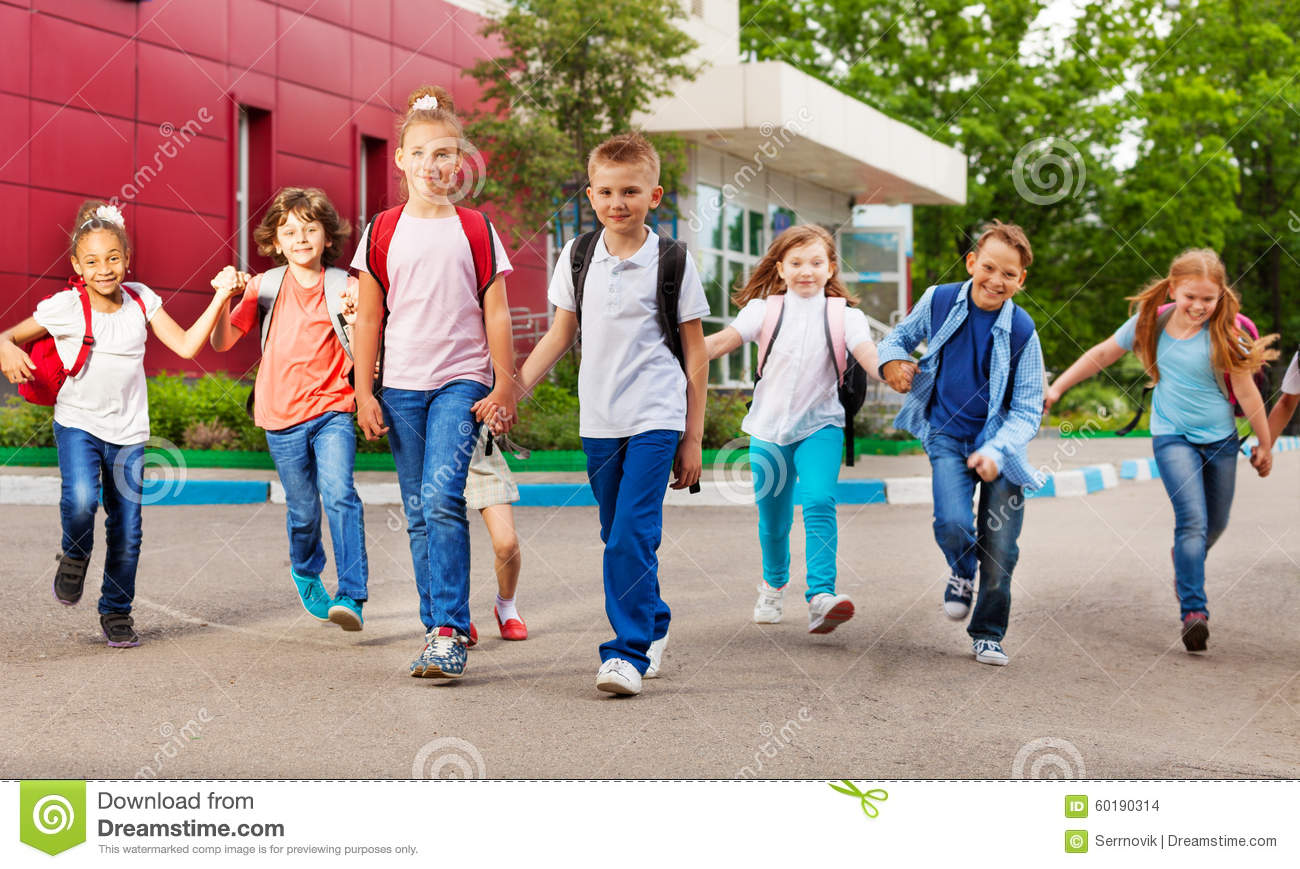 Row of happy kids with bags near school building
