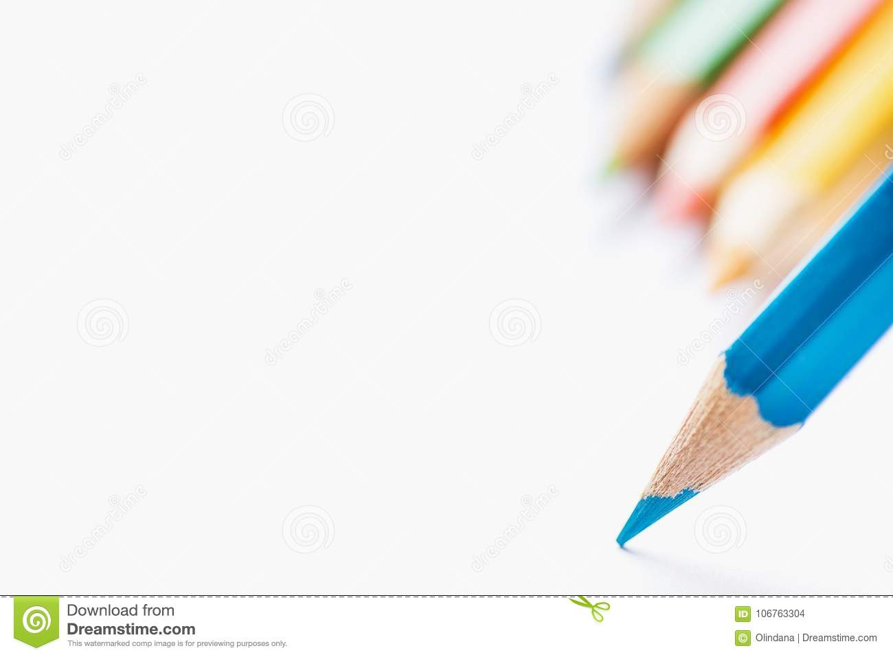 Row of Multicolored Pencils in Background Single Blue Sharp Pencil Pointing with Tip to Blank White Paper. Beginning of Drawing