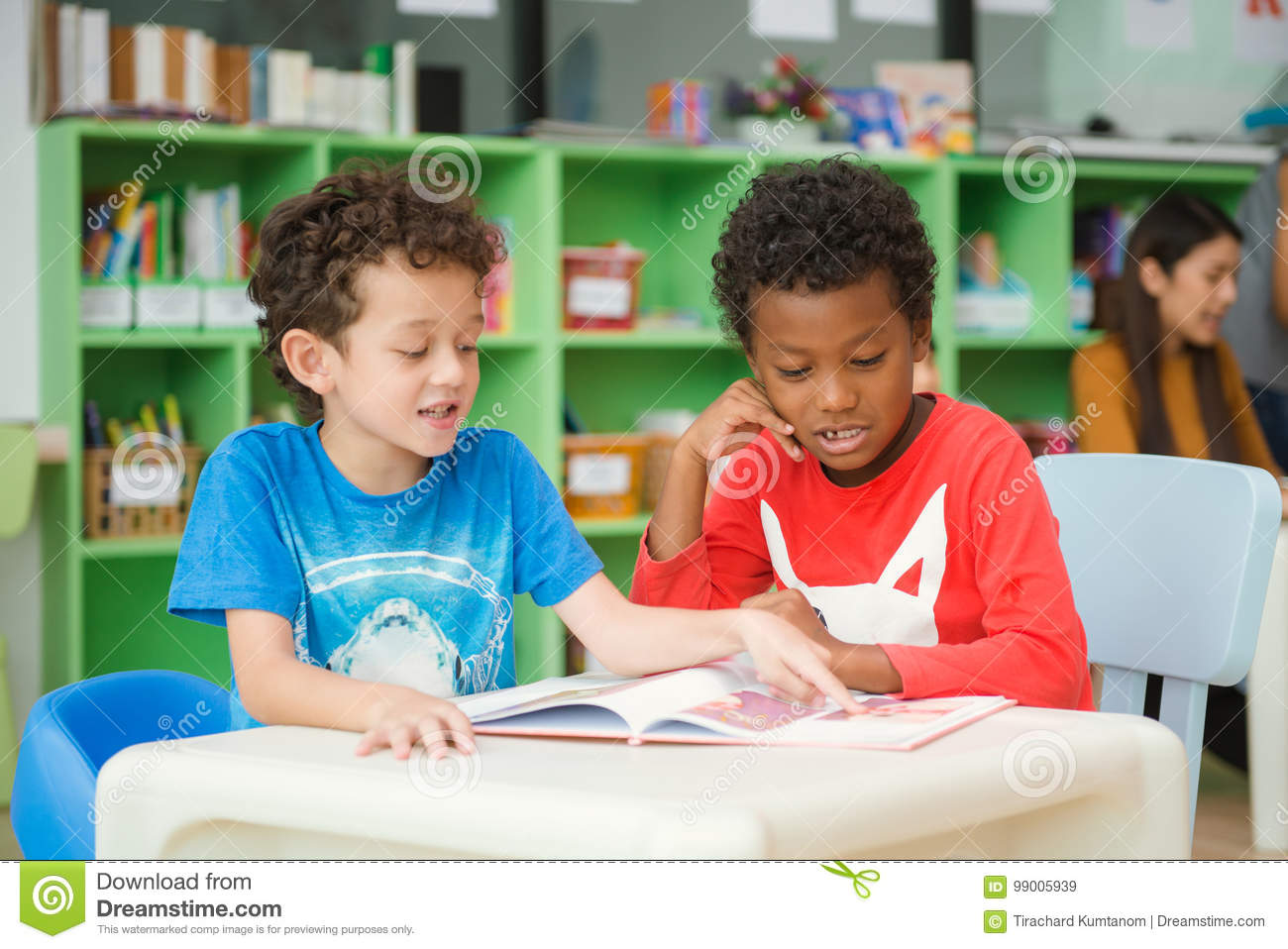 Row of multiethnic elementary students reading book in classroom.