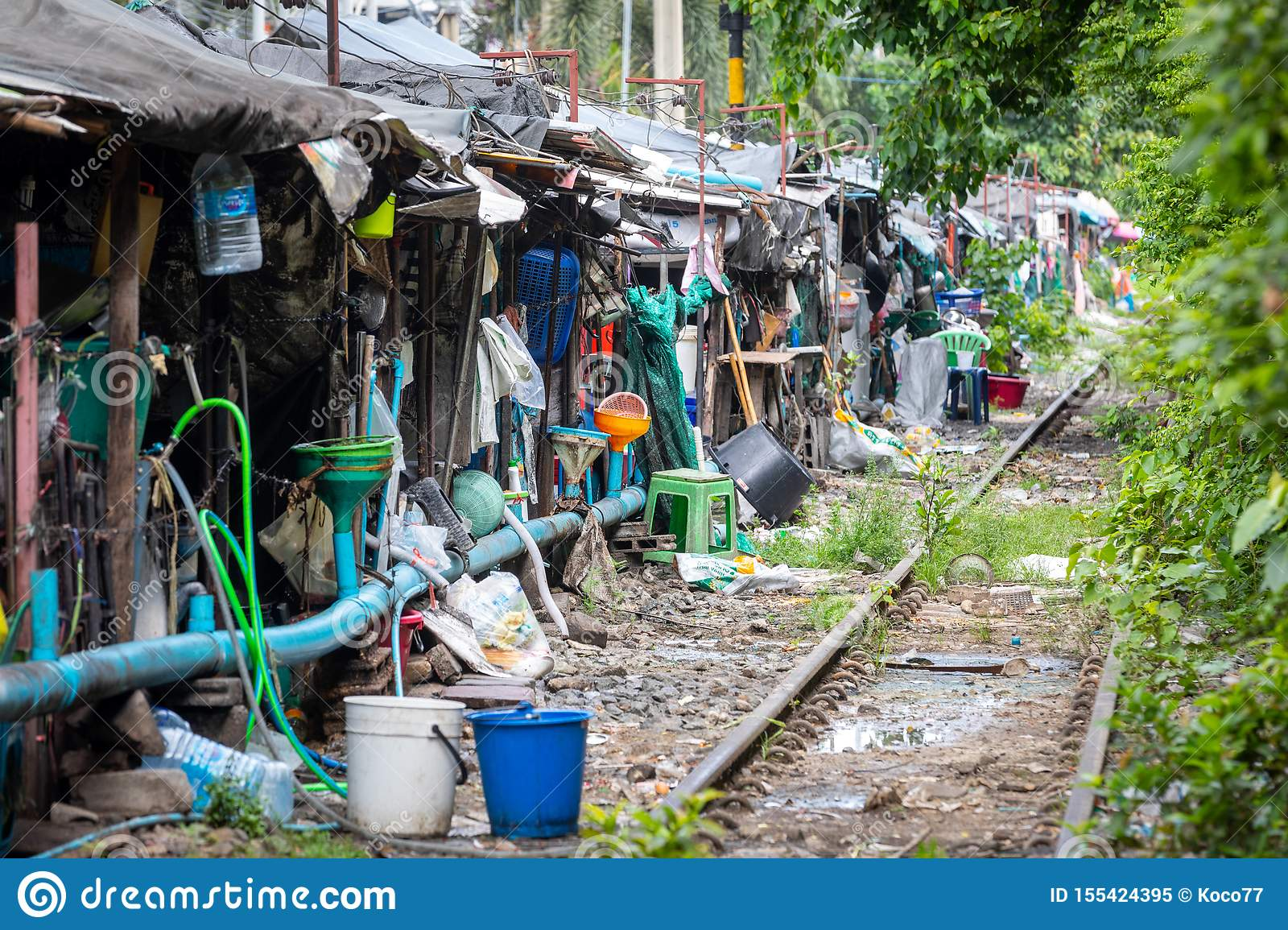 Row of shacks with small businesses beside the tracks of a train in central Bangkok in Thailand.