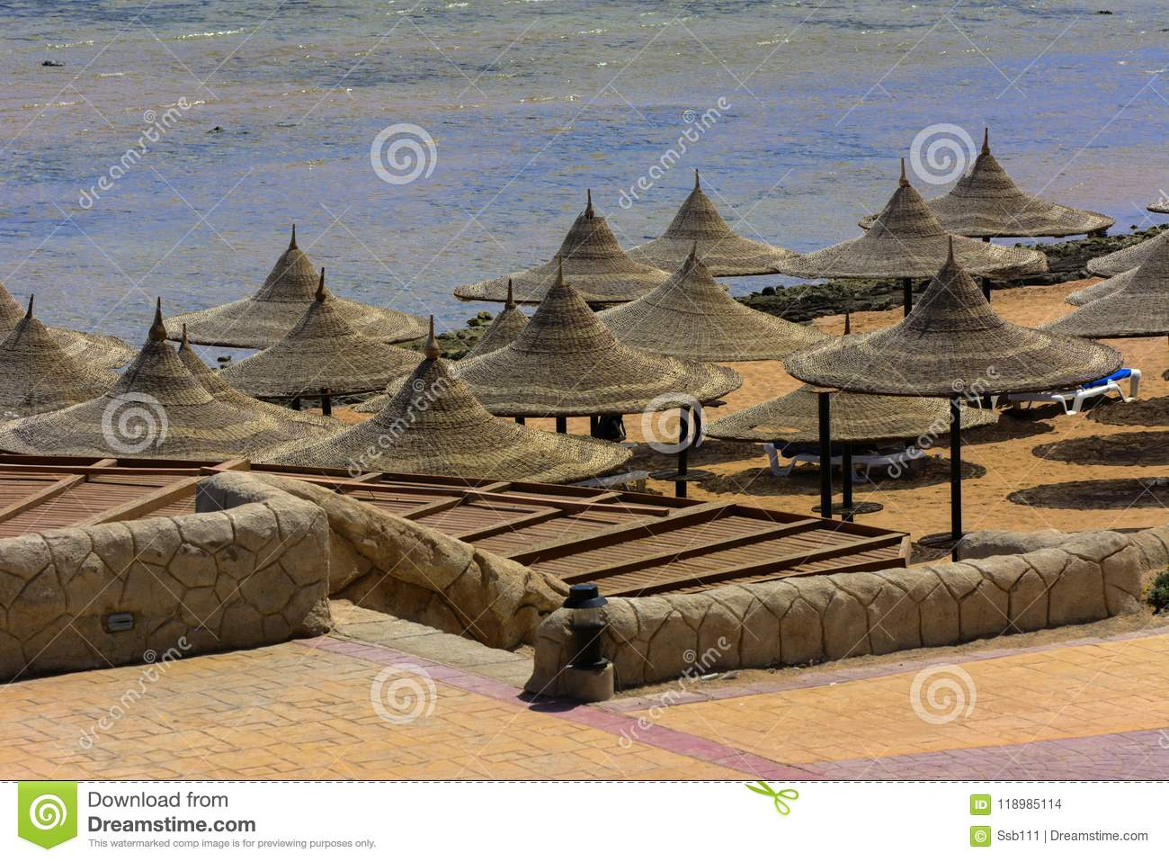 A Row Of Straw Umbrellas To Protect Against Overheating And