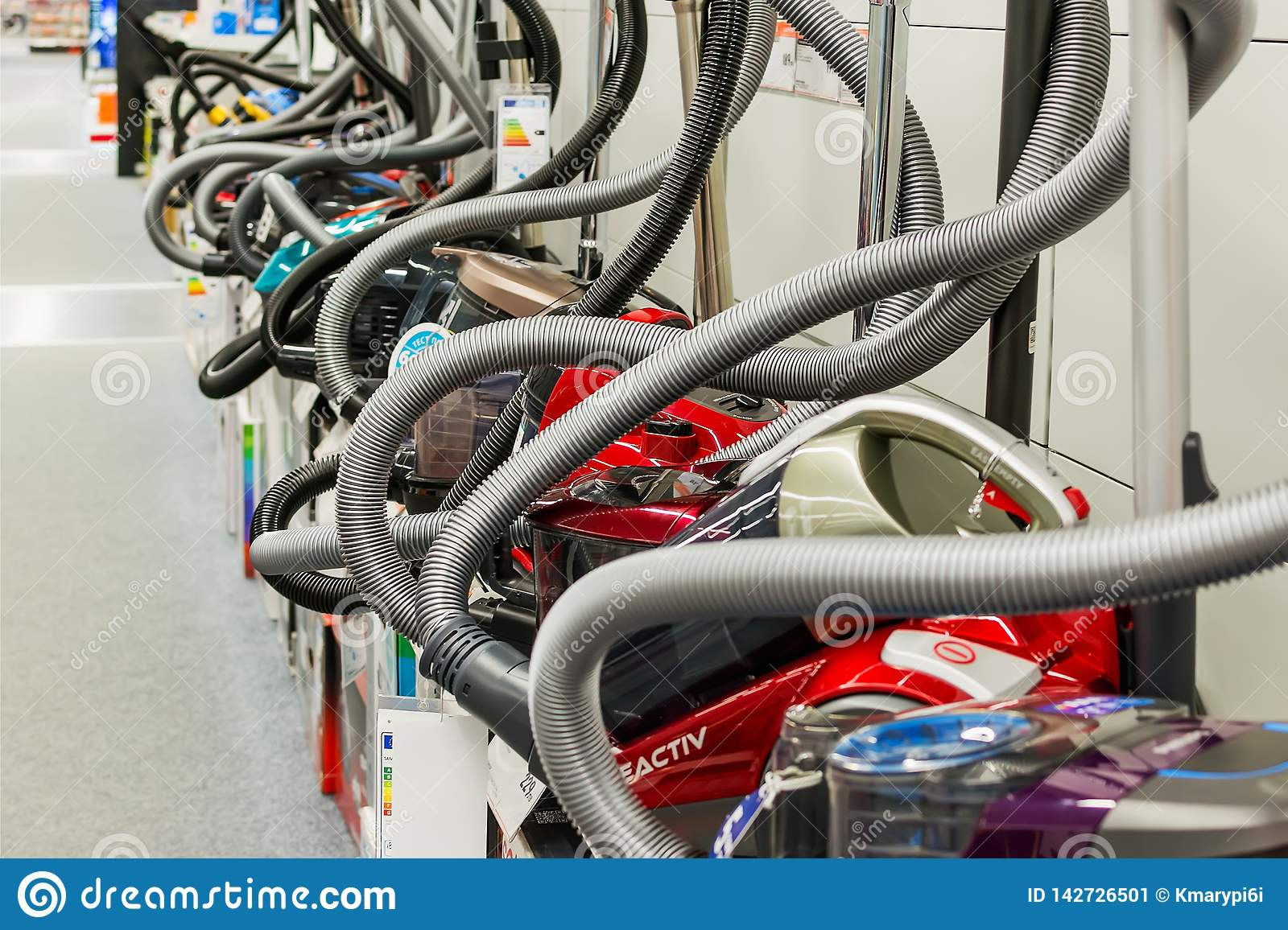 Row of vacuum cleaners of different manufacturers in the appliances store. Sale of household electrical equipment in the
