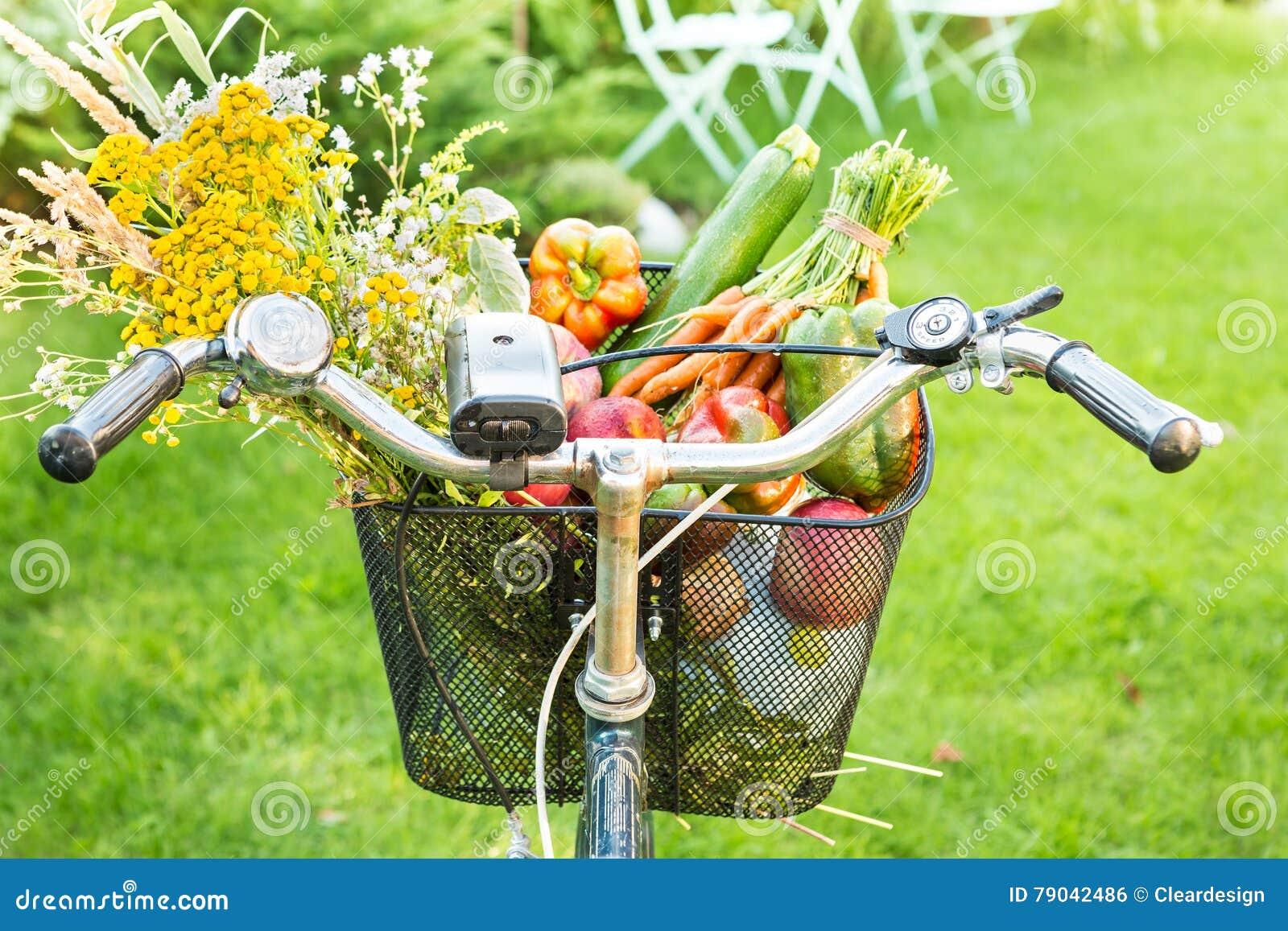 Rowerowy kosz wypełniający z świeżymi warzywami i kwiatami