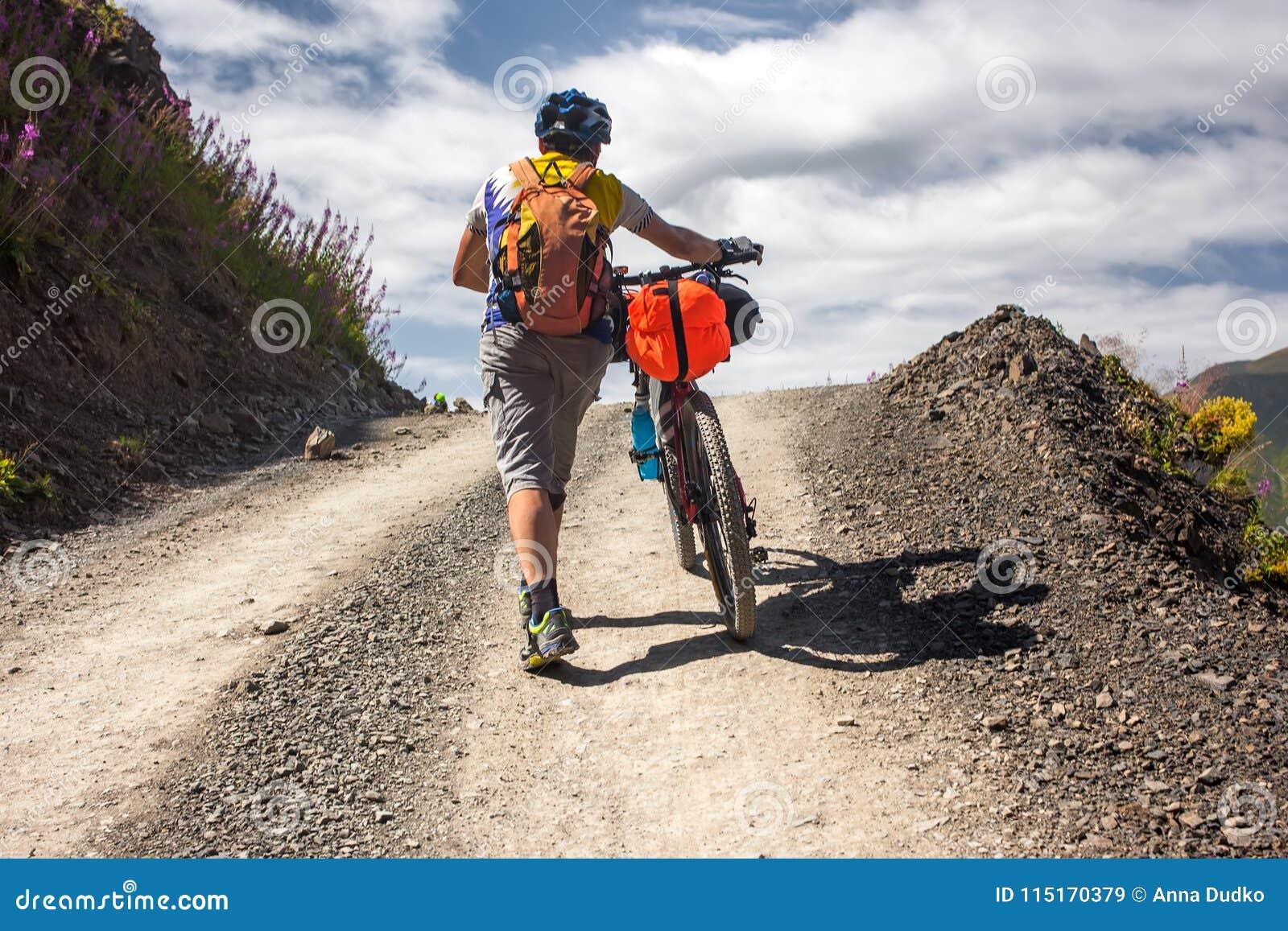 Rowerzysta pcha jego bicykl up w wysokich Kaukaz górach