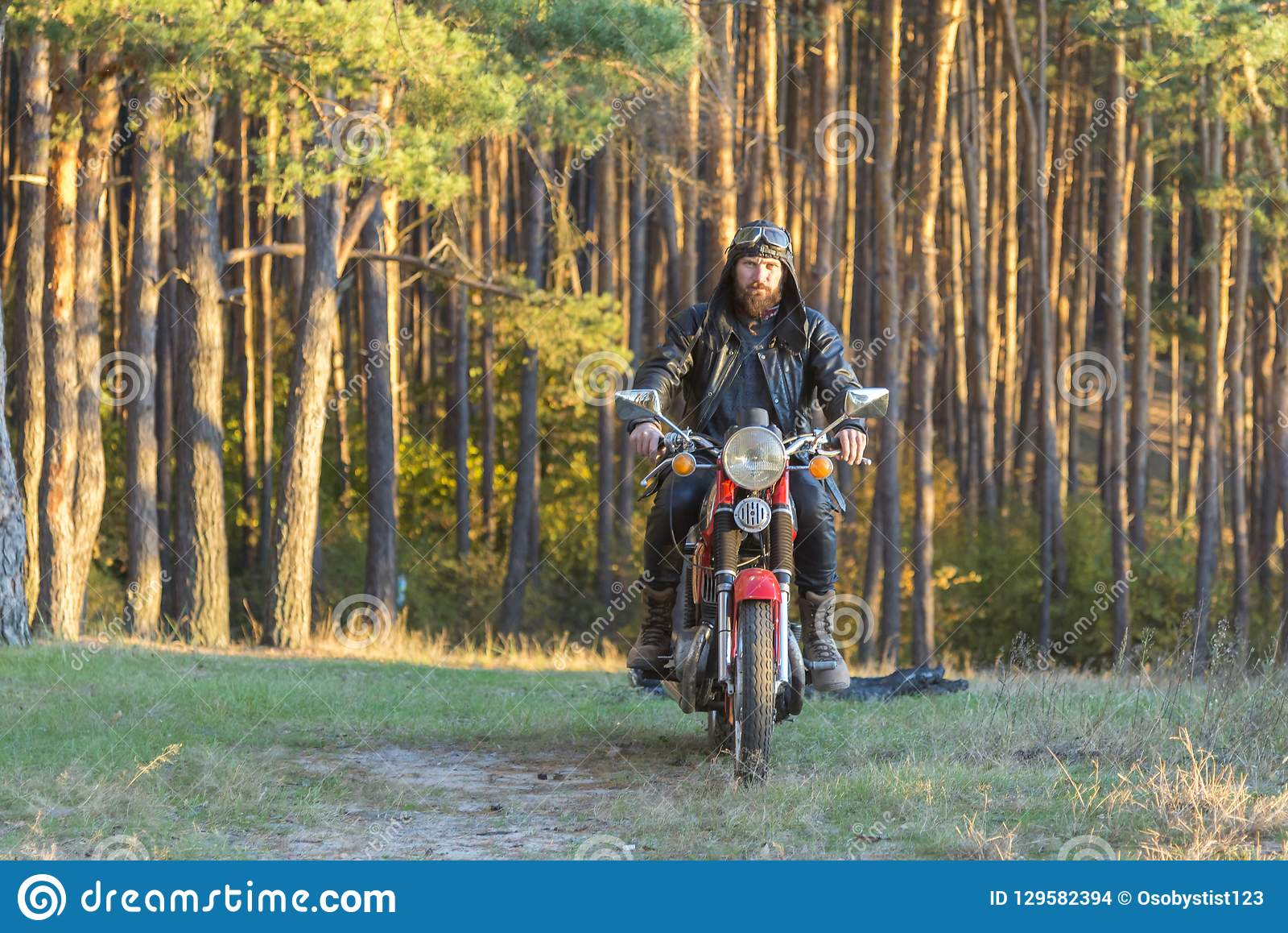 Rowerzysta w skórzanej kurtce i hełm na retro motocyklu w lesie