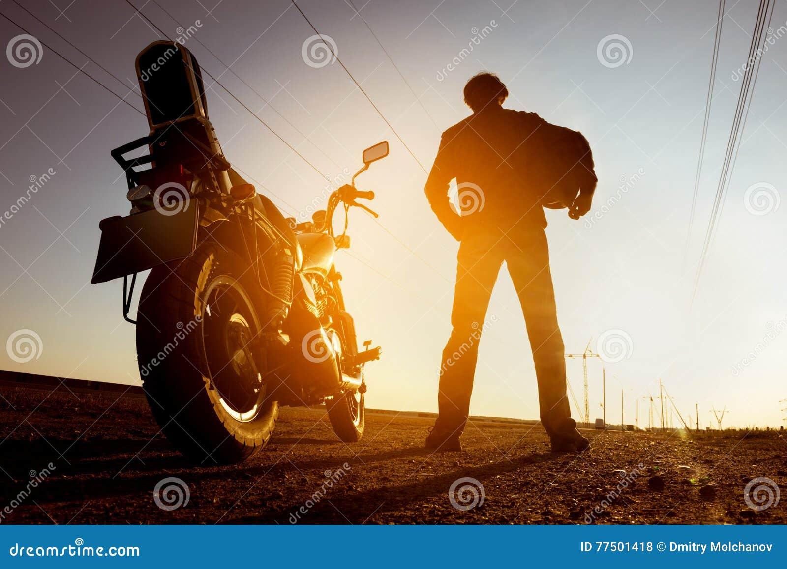 Rowerzysta z motocykli/lów stojakami na zmierzchu tła nieba drodze