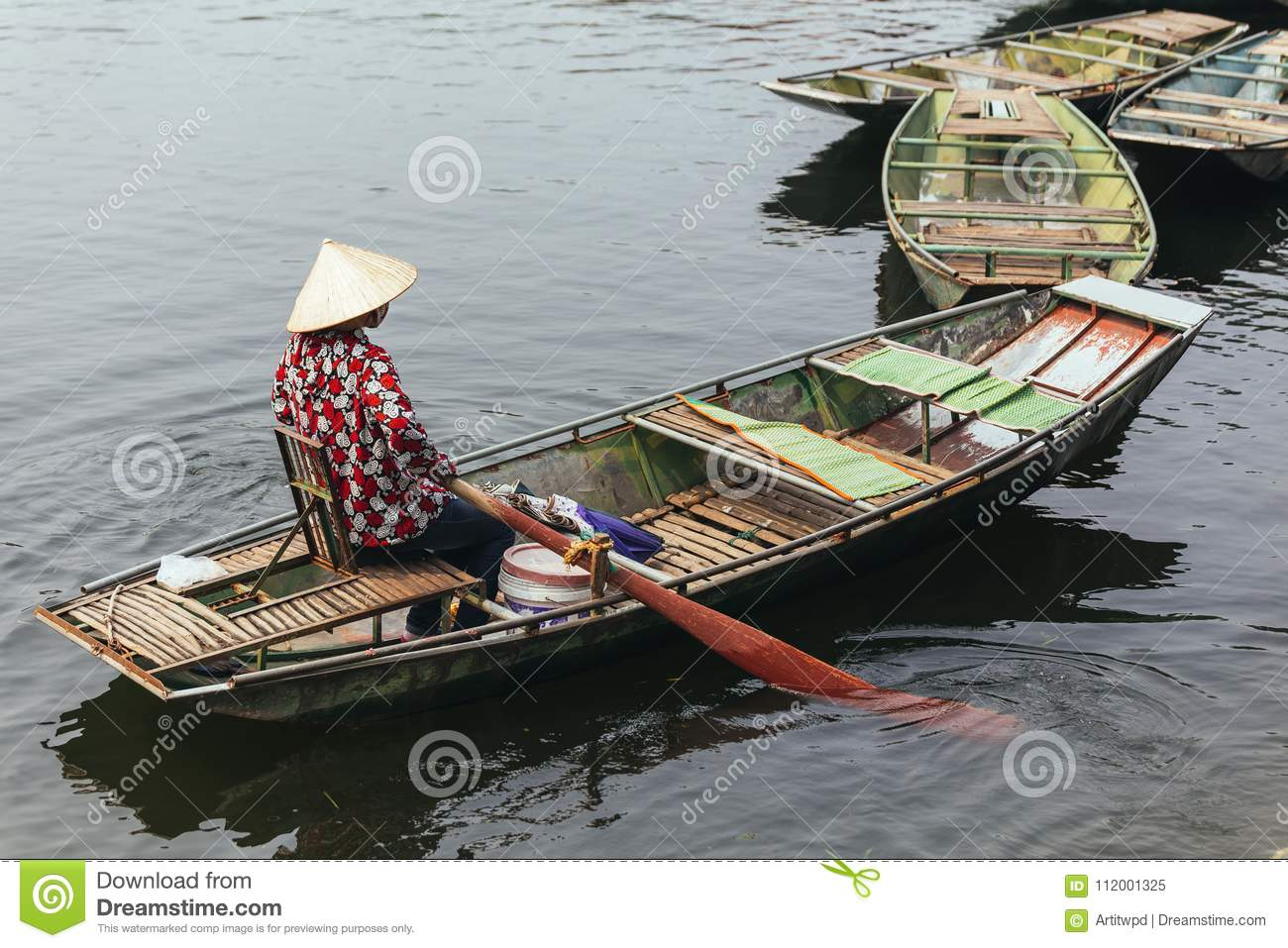 Rowing boat woman wearing red and white colors shirt, conical hat and mouth mask sitting in a boat with paddles over the river.