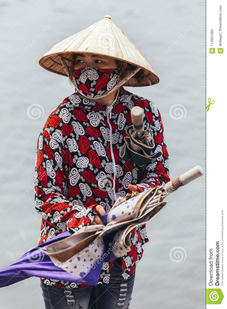 Rowing boat woman wearing red and white colors shirt, conical hat and mouth mask stand and carry umbrellas in Ninh Binh, Vietnam