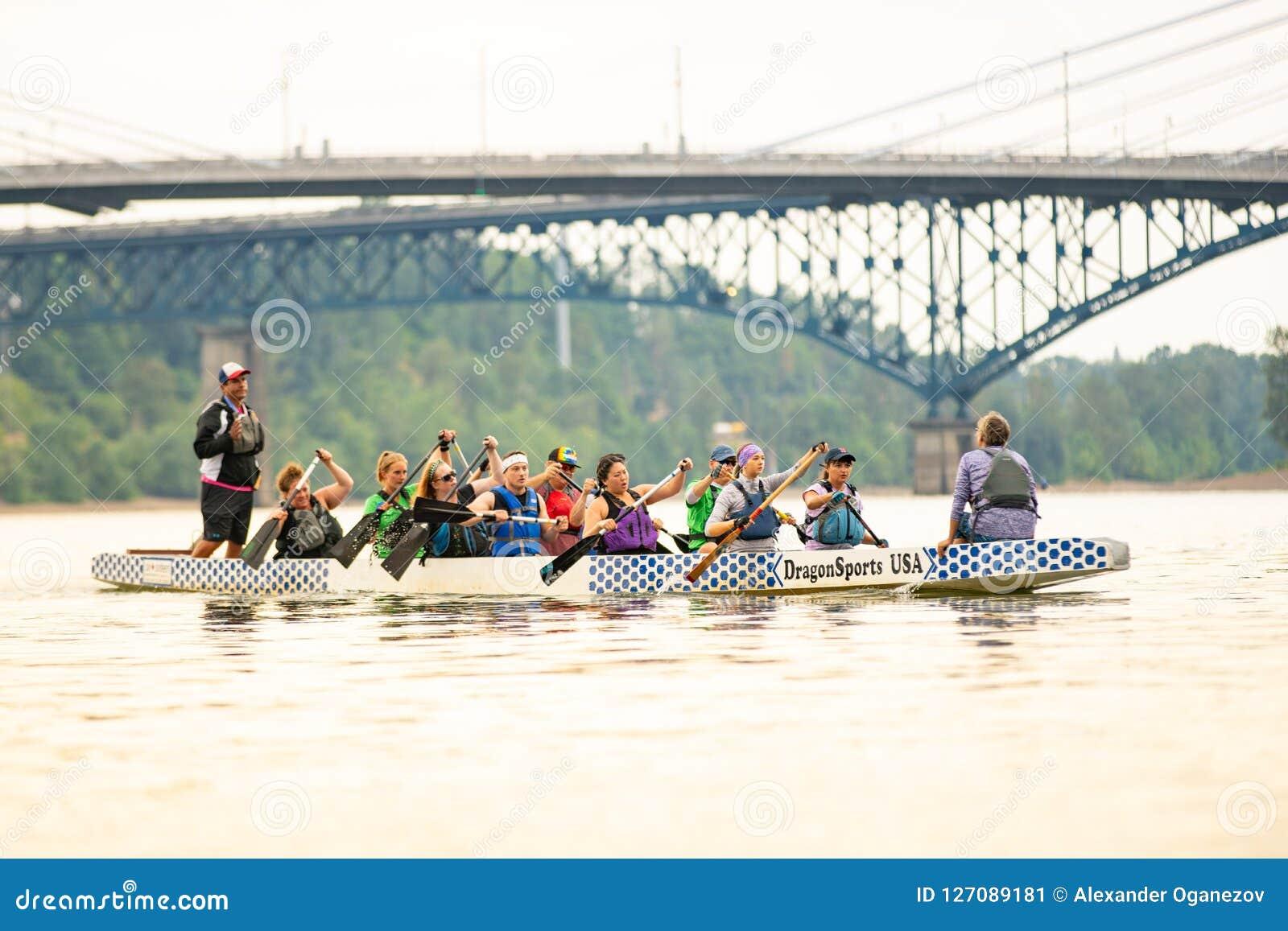 Rowing diverso grande del grupo de personas en el kajak grande