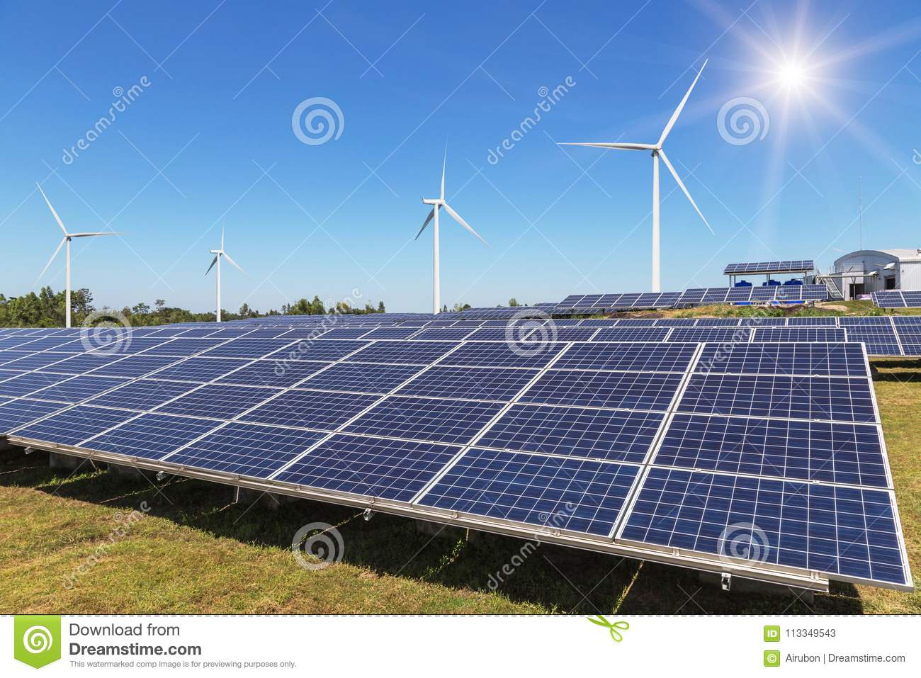 Rows array of polycrystalline silicon solar panels and wind turbines generating electricity in hybrid power plant systems station