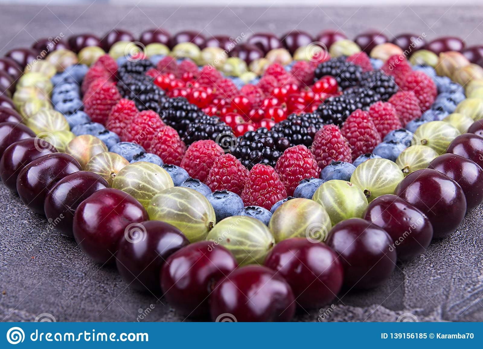 Rows of assorted fruits and berries: sweet cherry, bluberries, raspberries, red and black currant, blackberries. Helthy eating