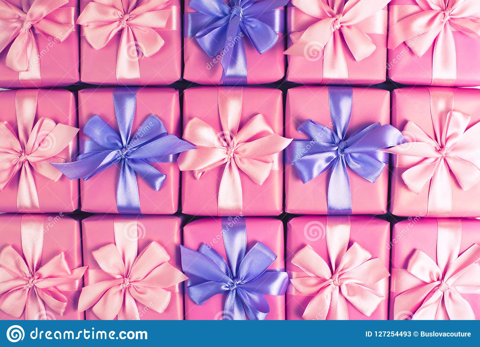 Rows of boxes with gifts decoration ribbon satin bow pink A top view of Flat lay toning