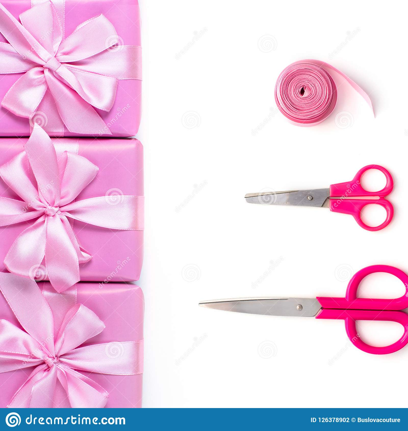Rows of boxes six with gifts decoration ribbon satin bow scissors pink A top view of Flat lay