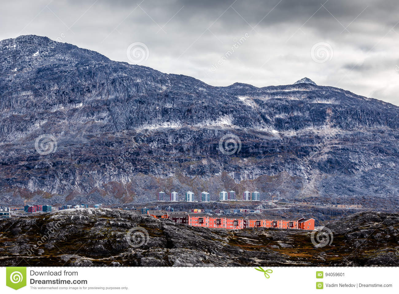 Rows of colorful modern Inuit houses among mossy stones with grey steep slopes of Little Malene mountain in
