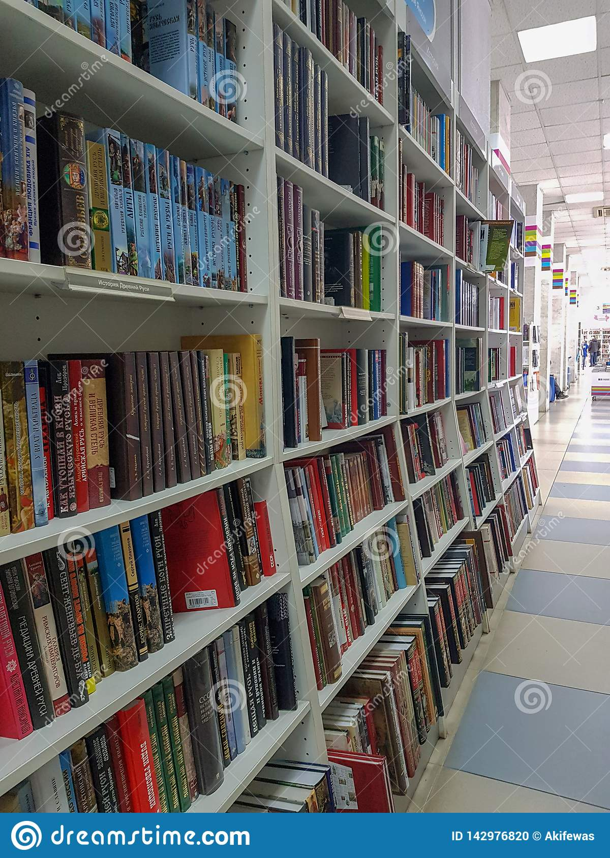 Rows of different colorful books lying on the shelves in the modern bookshop