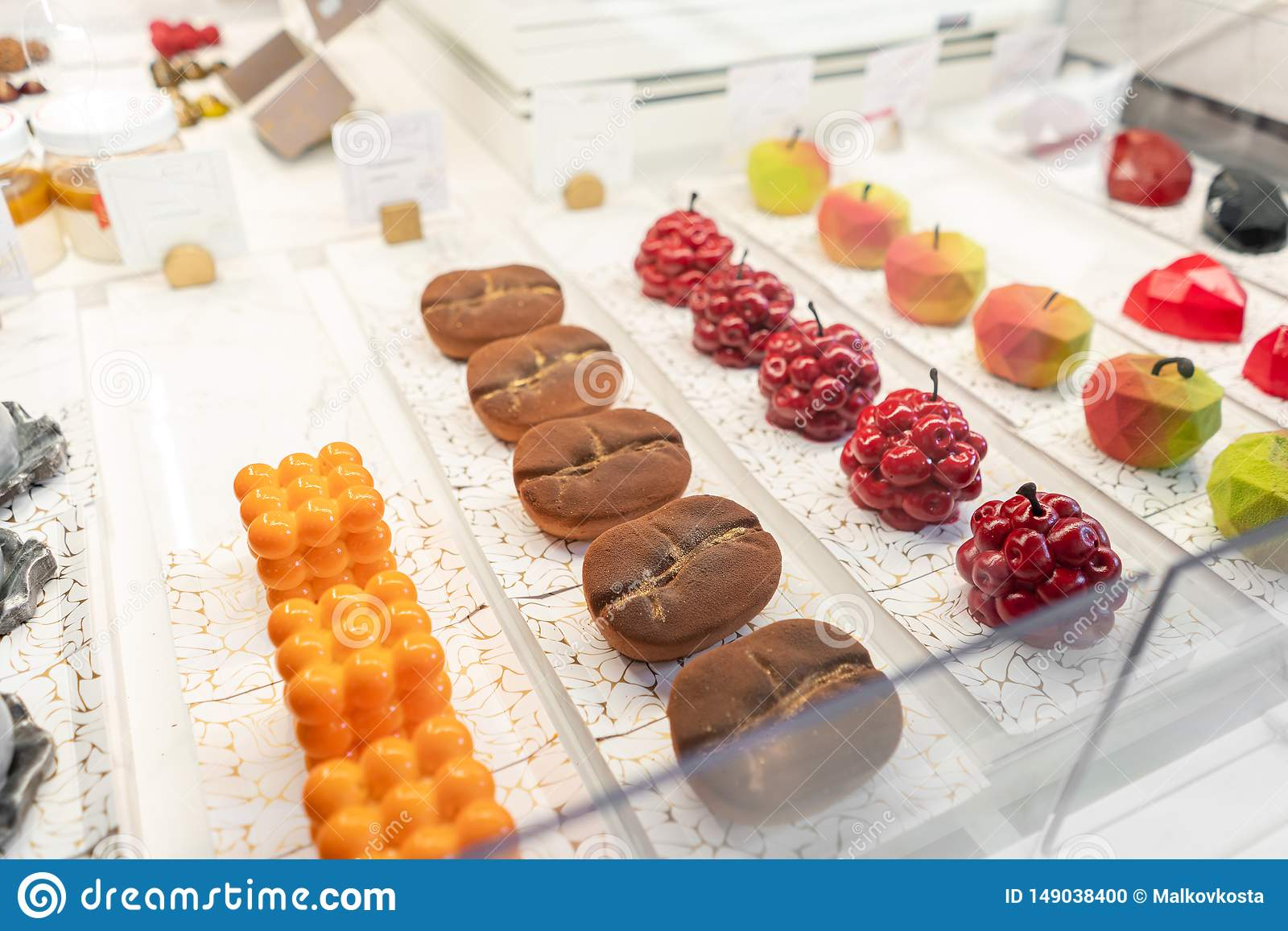 Rows of multicolored cakes and desserts in the window of a pastry shop. Modern mousse dessert, sweet snack. in the form