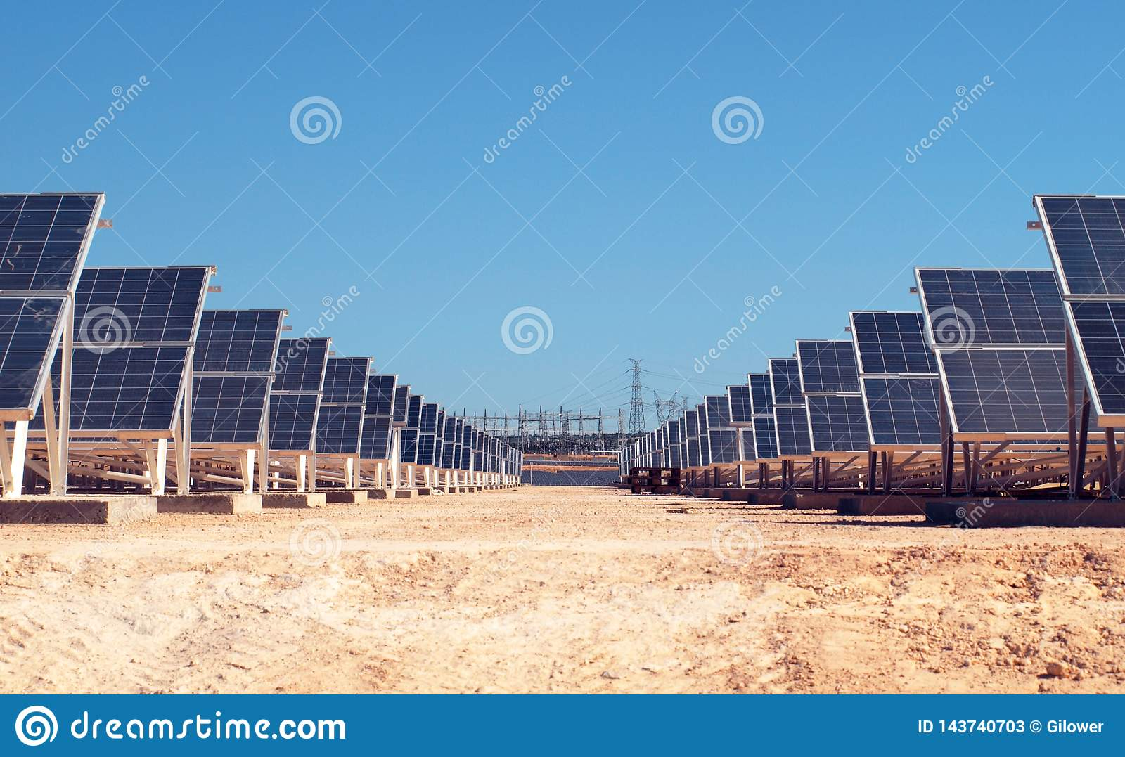 Solar field with electric power station in the background.