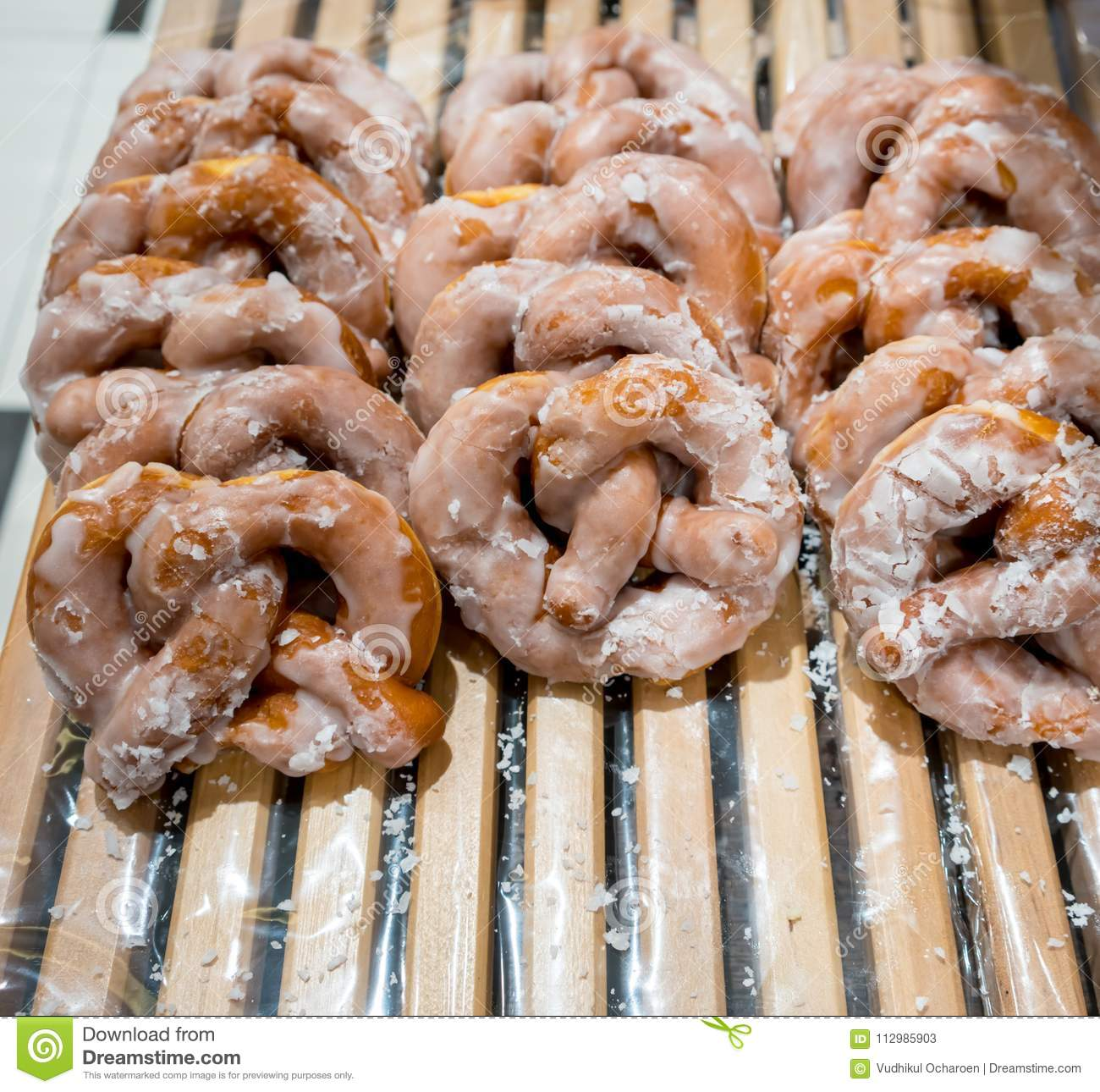 Rows of sugar syrup glazed pretzels on wooden rack in modern shop.
