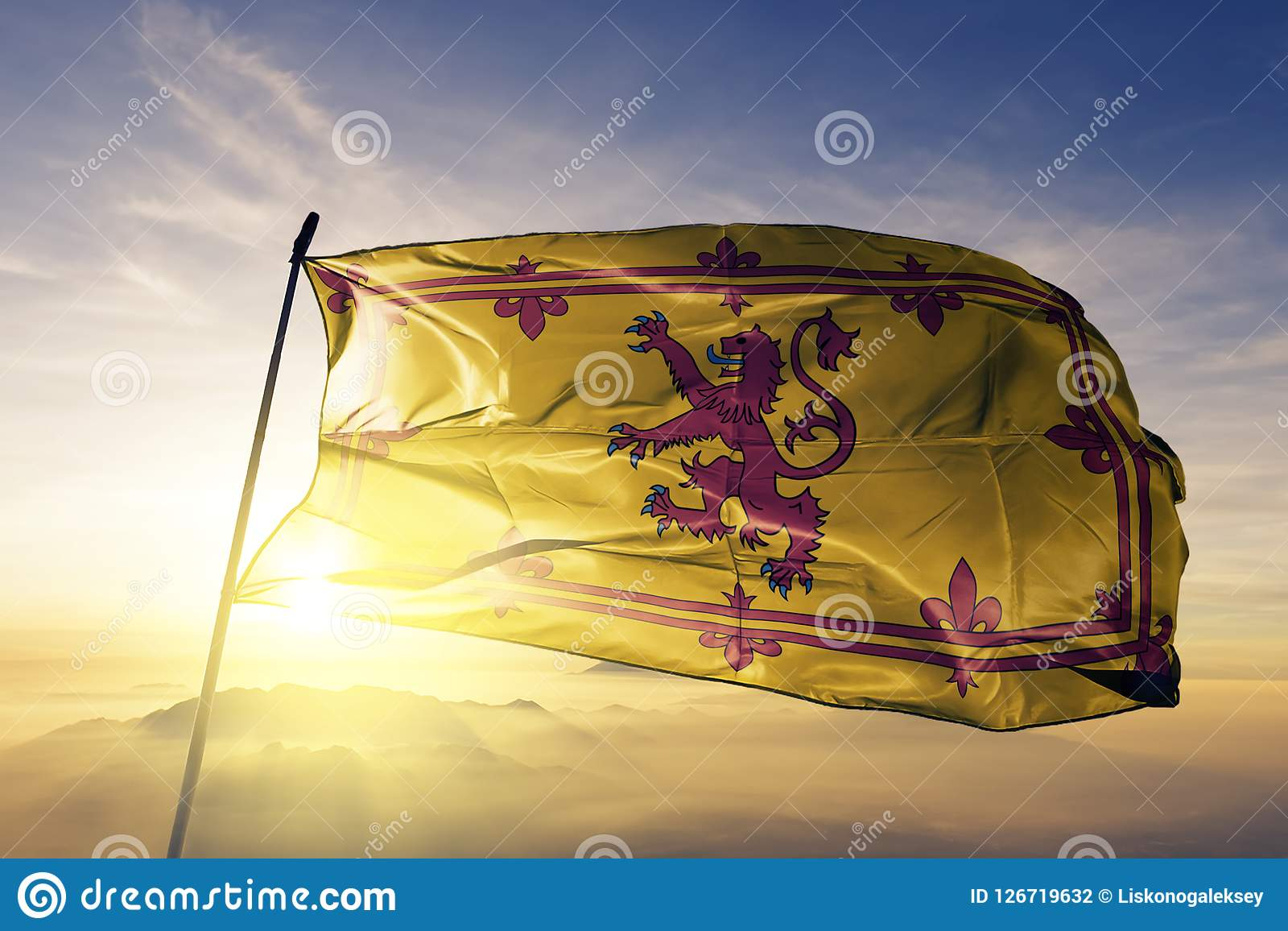 Royal Banner of Scotland flag textile cloth fabric waving on the top sunrise mist fog