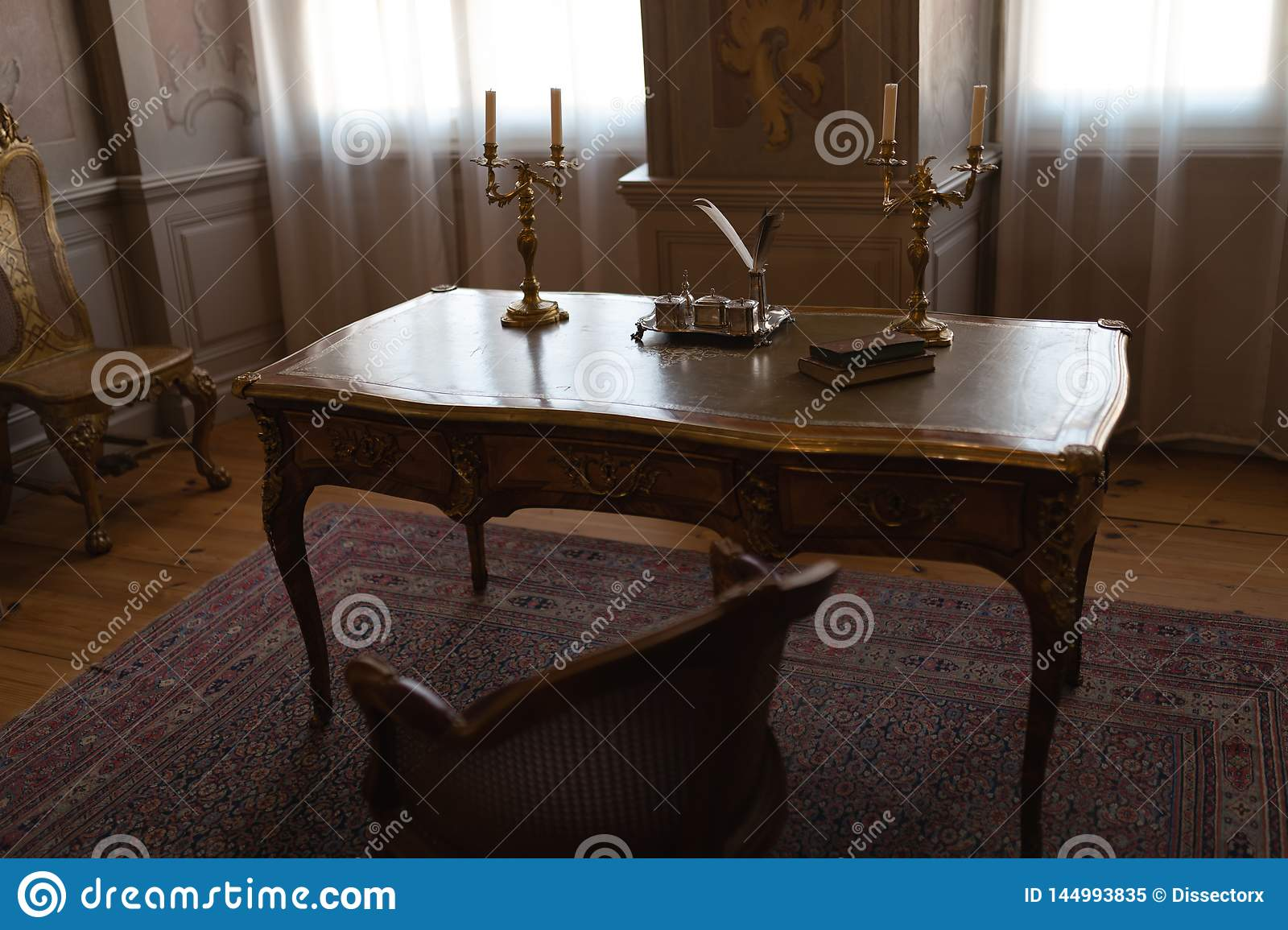 Royal palace table in a cabinet room with chairs and pen and ink
