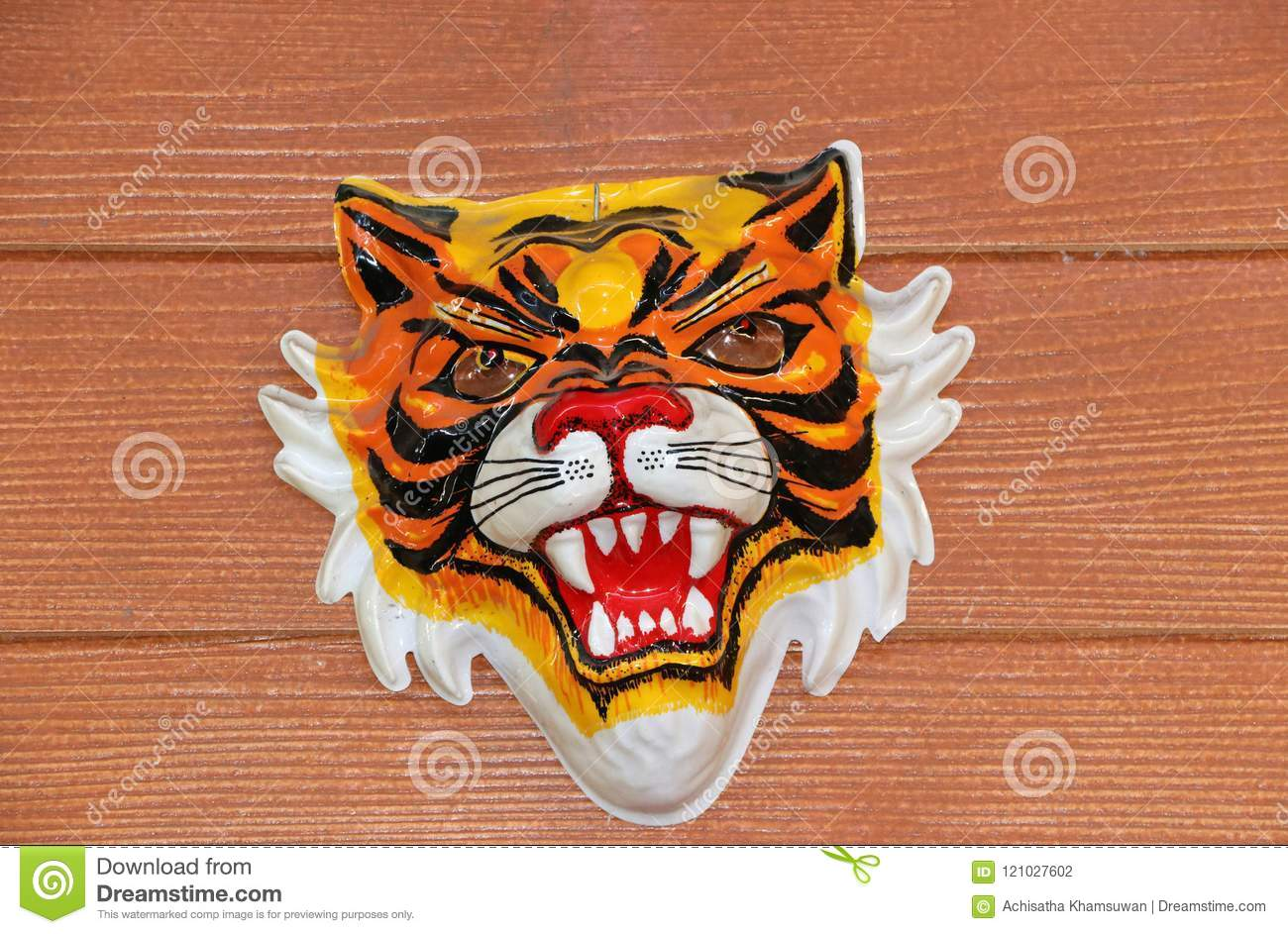 Royal Tiger Plastic Mask Hanging On The Brown Fiber Cement Wall