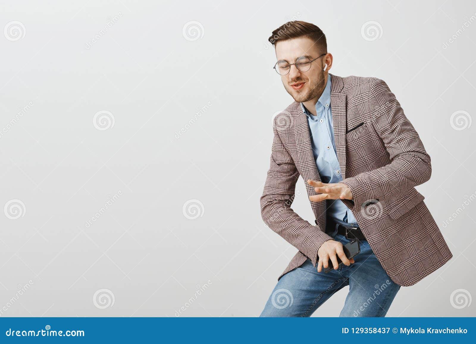 Rozbawiony atrakcyjny elegancki facet niesie daleko od z chłodno muzycznym chylenie puszkiem w tana ruchu chwiania rękach kawałek