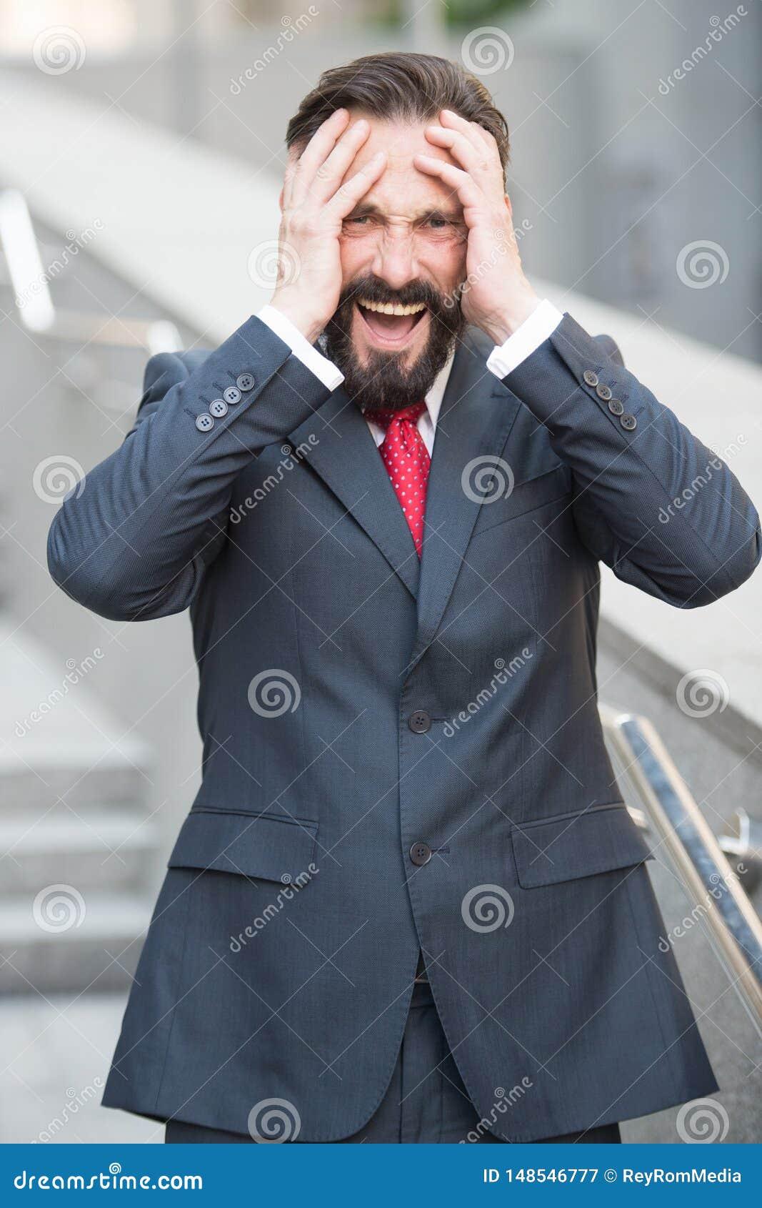 Rozczarowany biznesmen krzyczy z rękami na jego głowę