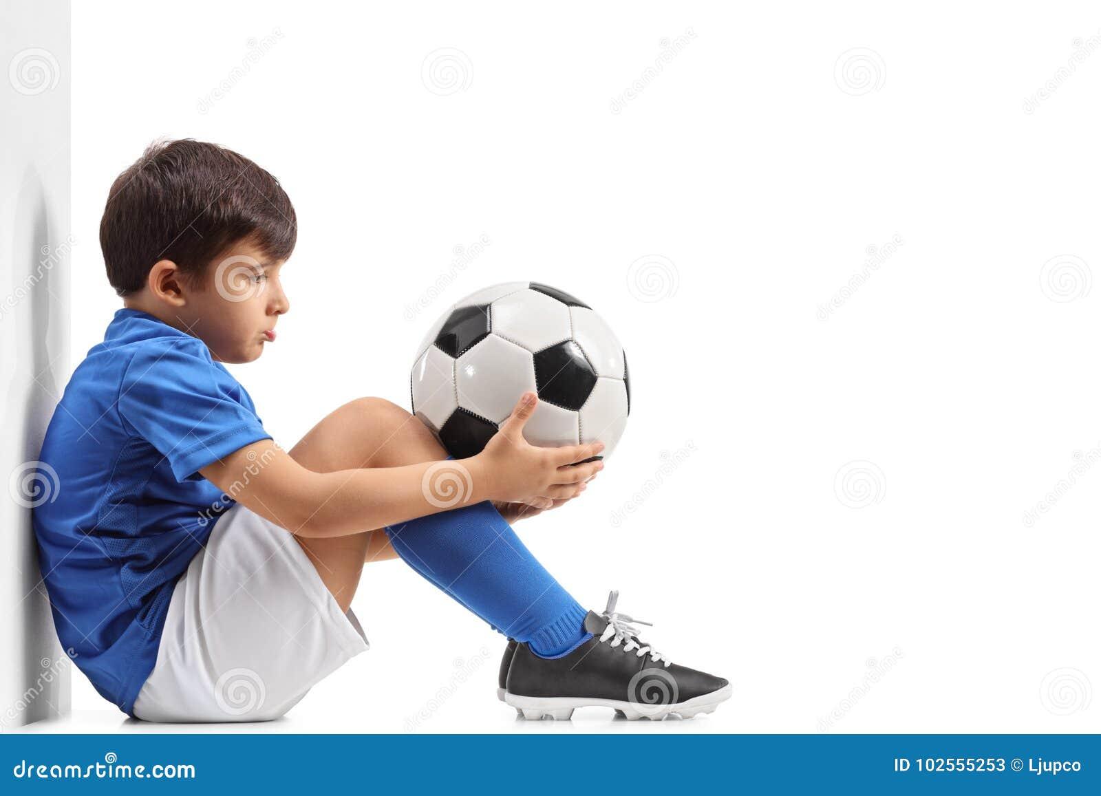 Rozczarowany mały futbolista opiera przeciw ścianie