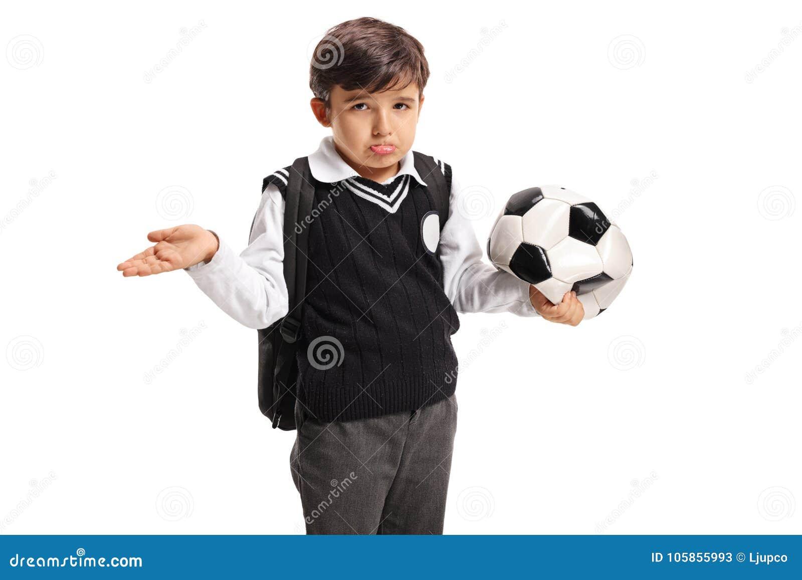 Rozczarowany mały uczeń trzyma deflated futbol