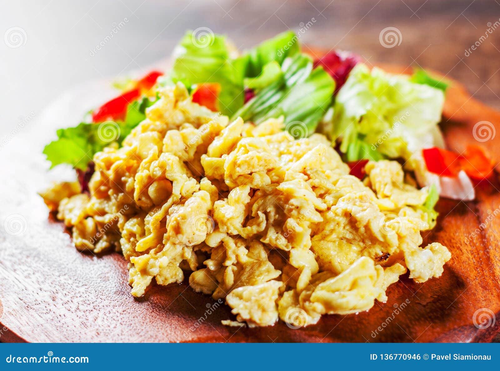 Rozdrapani jajka z różnorodną świeżą mieszanki sałatką opuszczają na drewnianym stole