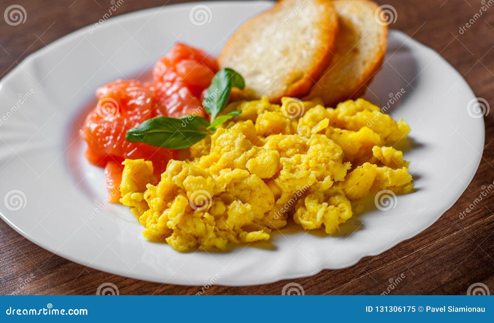 Rozdrapani jajka z uwędzonym łososiem i grzanką w bielu talerzu na drewnianym stole