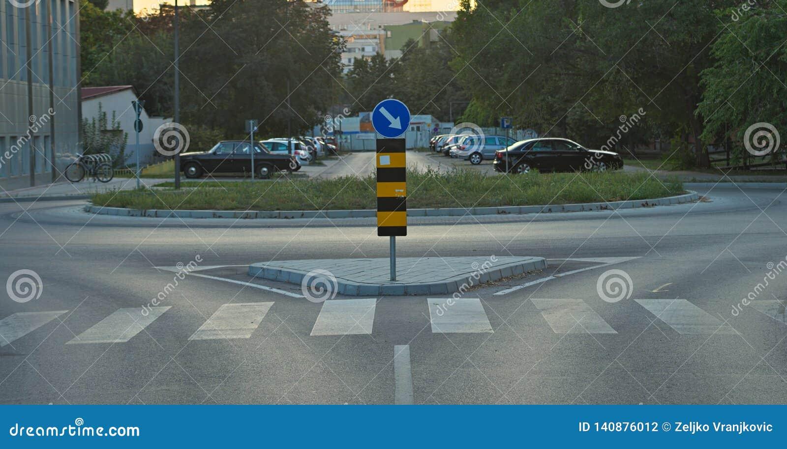 Rozdroże z ruchu drogowego znakiem i parking w tle