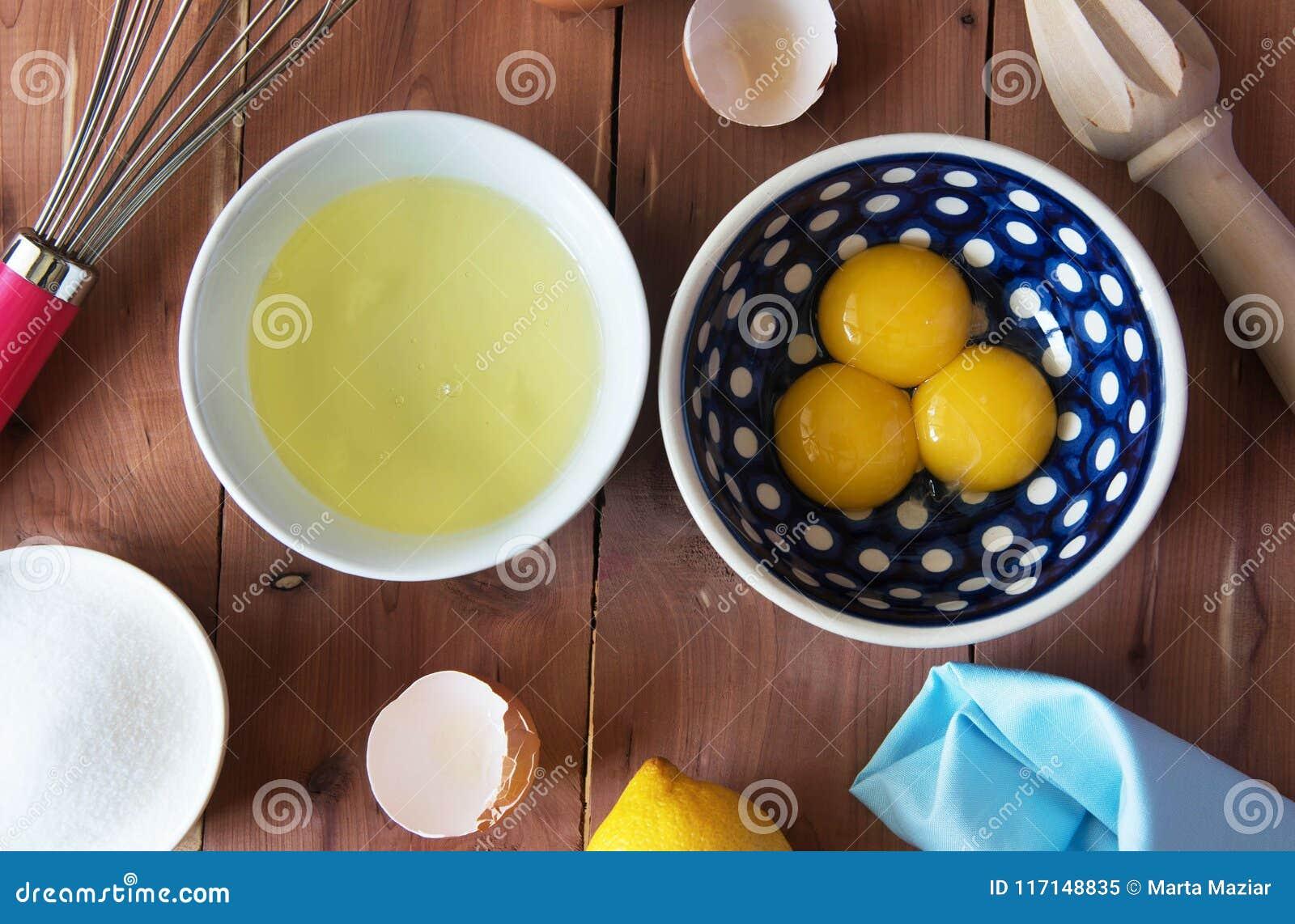 Rozdzielenie yolk jajko w małym pucharze i przygotowanie dla trzepać i jajeczni biel i yolks