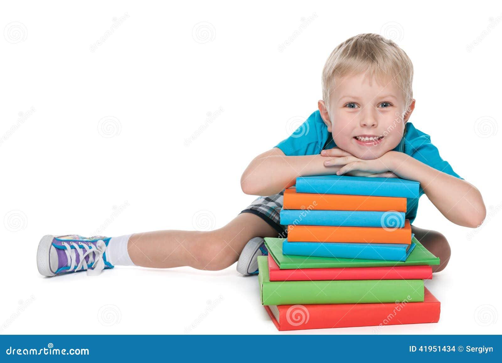Roześmiana śliczna chłopiec z książkami