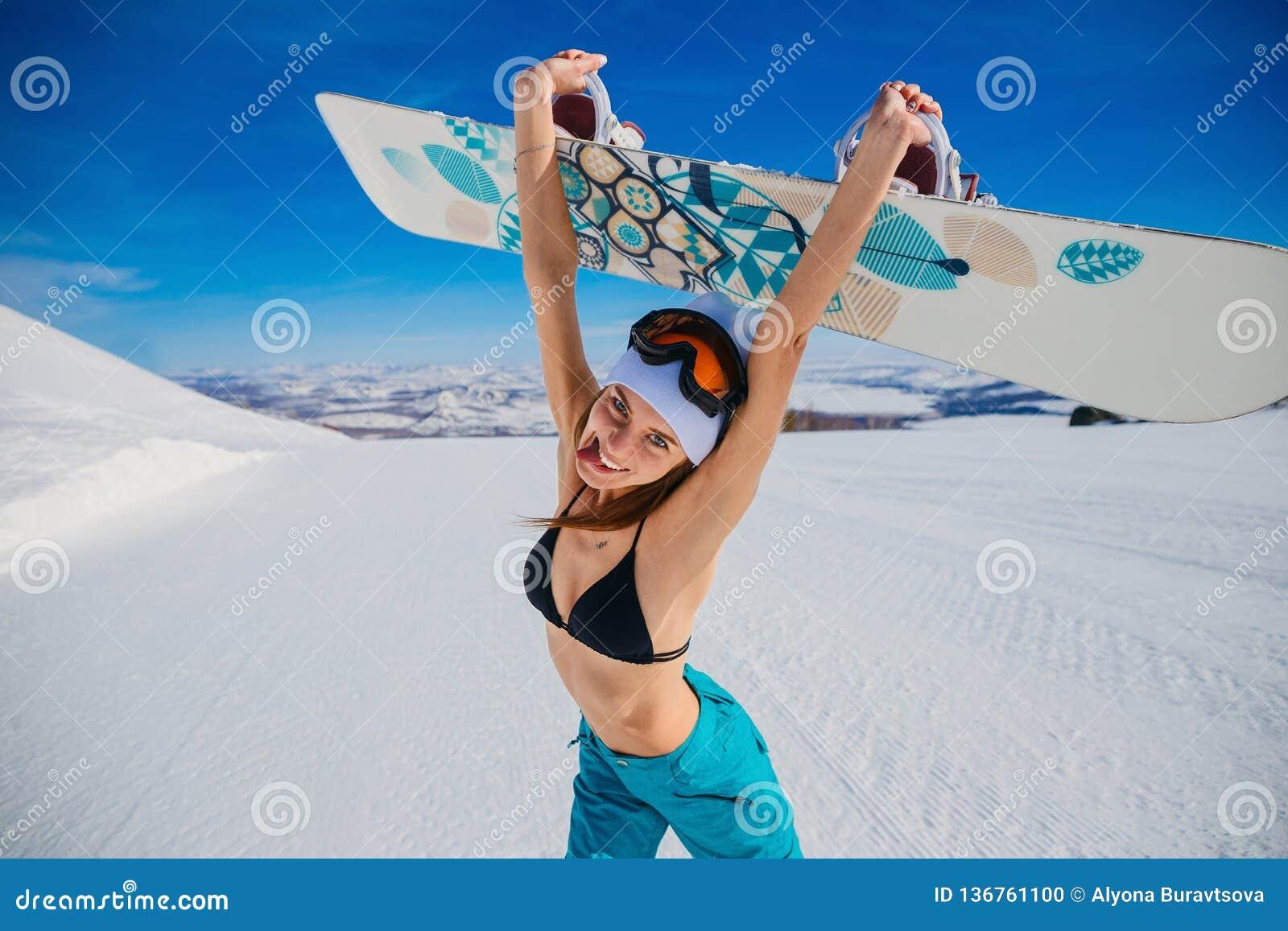 Roześmiana emocjonalna młoda kobieta trzyma snowboard w jej rękach w zimie w kapeluszu i swimsuit sport ekstremalny euphrates Kob