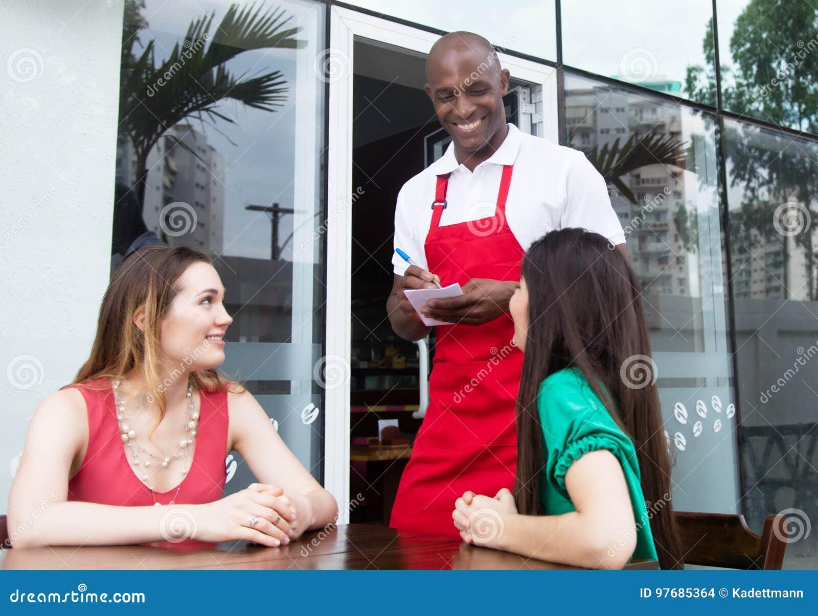 Roześmianego amerykanina afrykańskiego pochodzenia kelnera powitalni goście