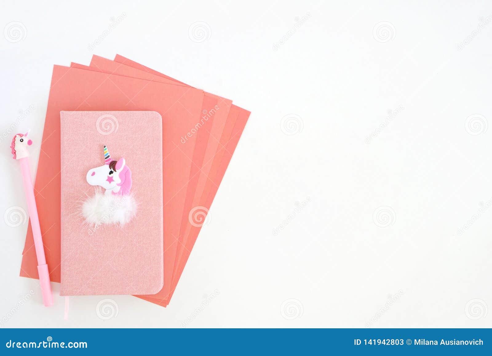Roze bladen van document, blocnote en pen met eenhoorn op witte achtergrond