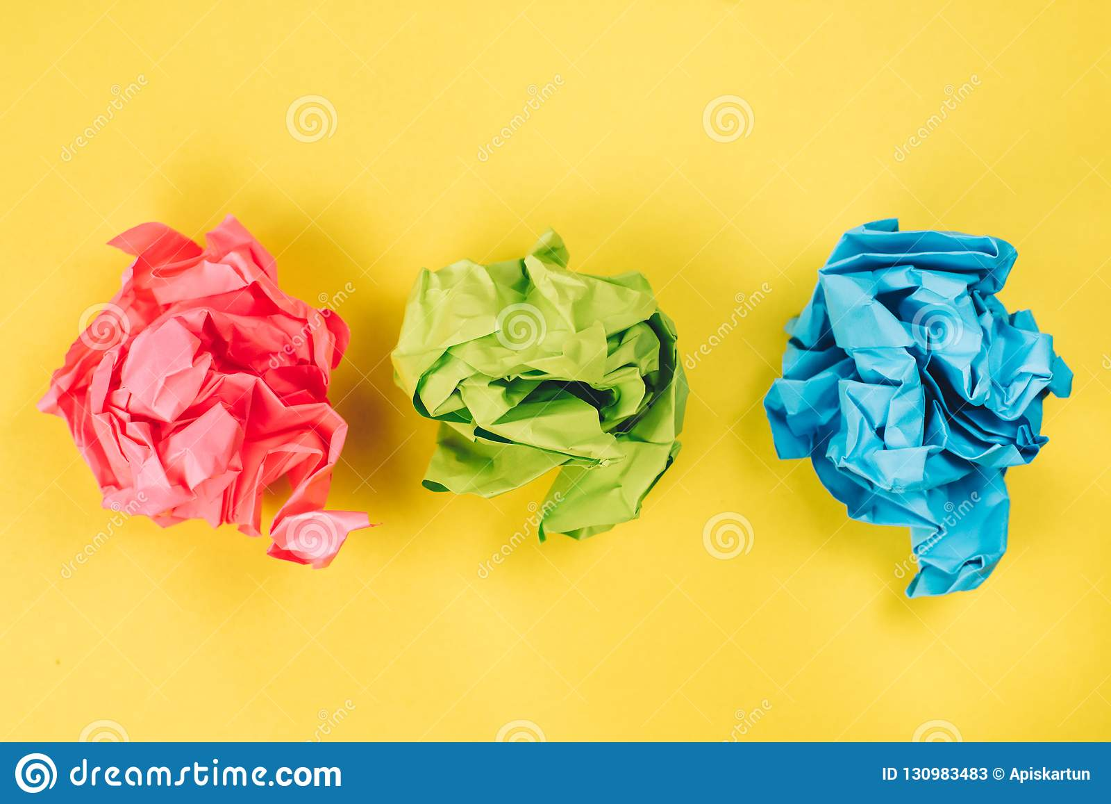 Roze, blauwe en groene verfrommelde document ballen op heldere gele achtergrond