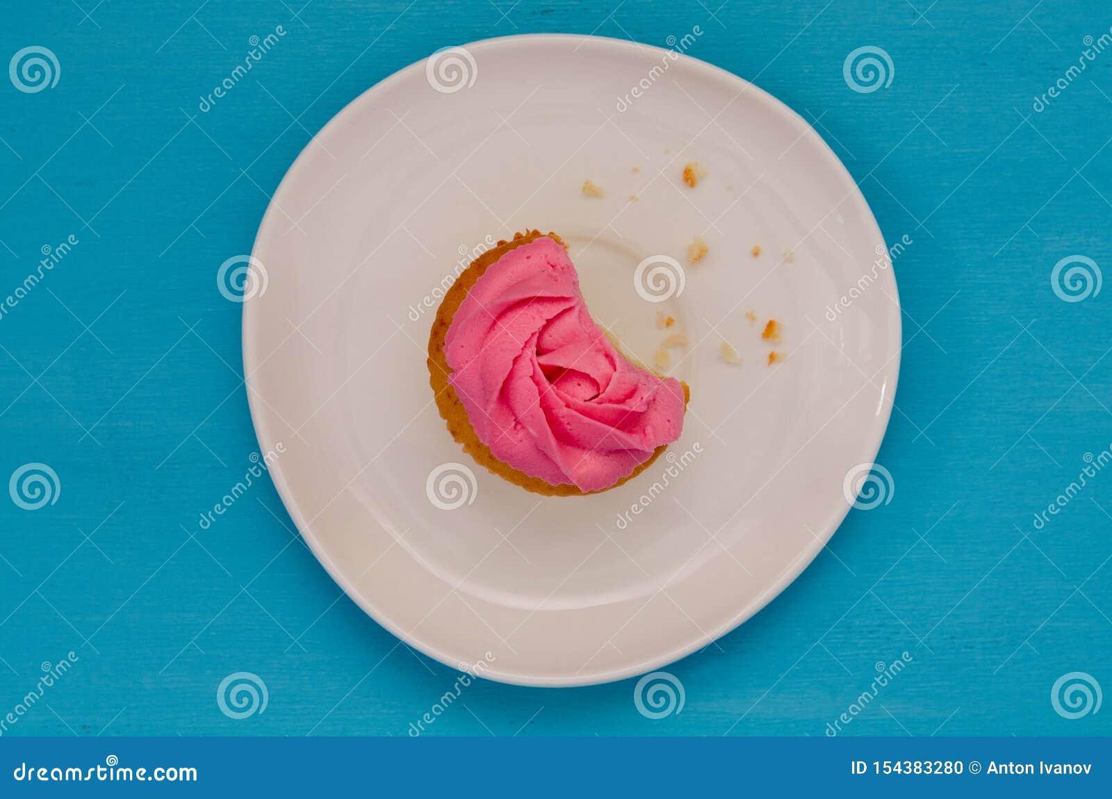 Roze cupcake op een plaat wordt op blauwe achtergrond wordt geïsoleerd gebeten die Heerlijke cake Hoogste mening