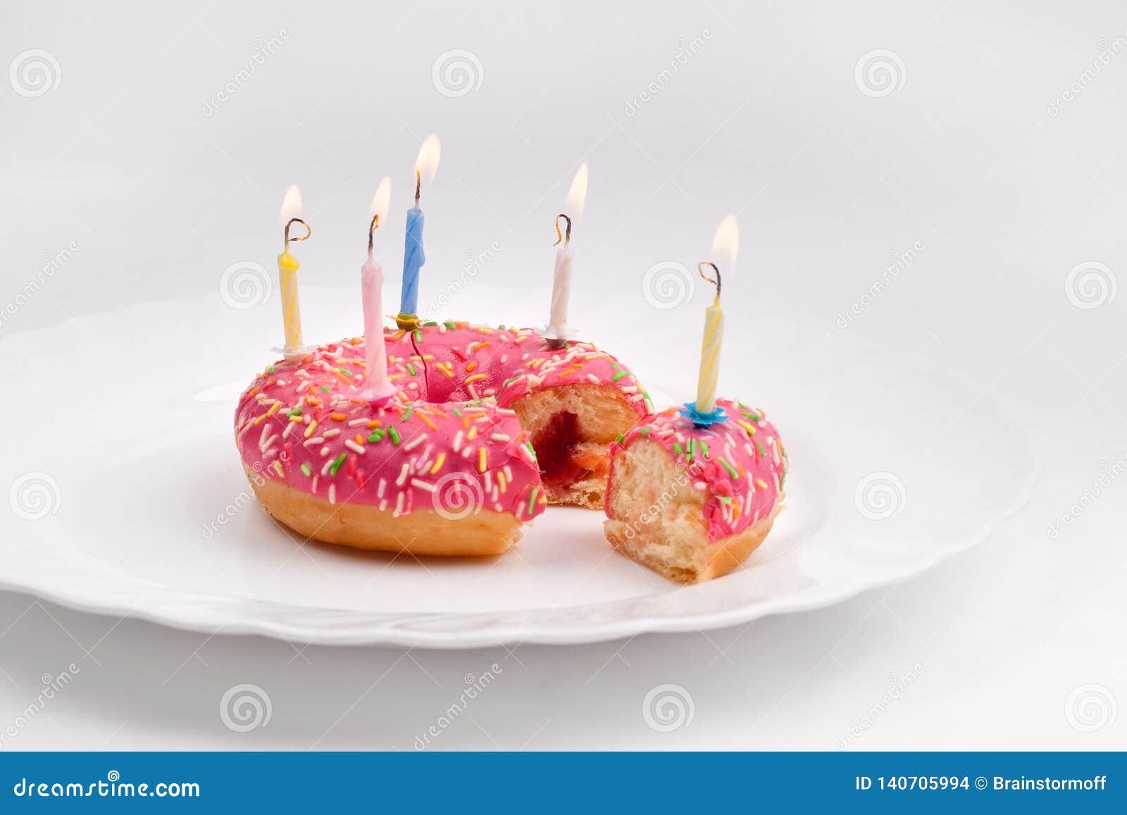Roze doughnut op witte plaat zoals verjaardagscake met kaarsen op witte achtergrond