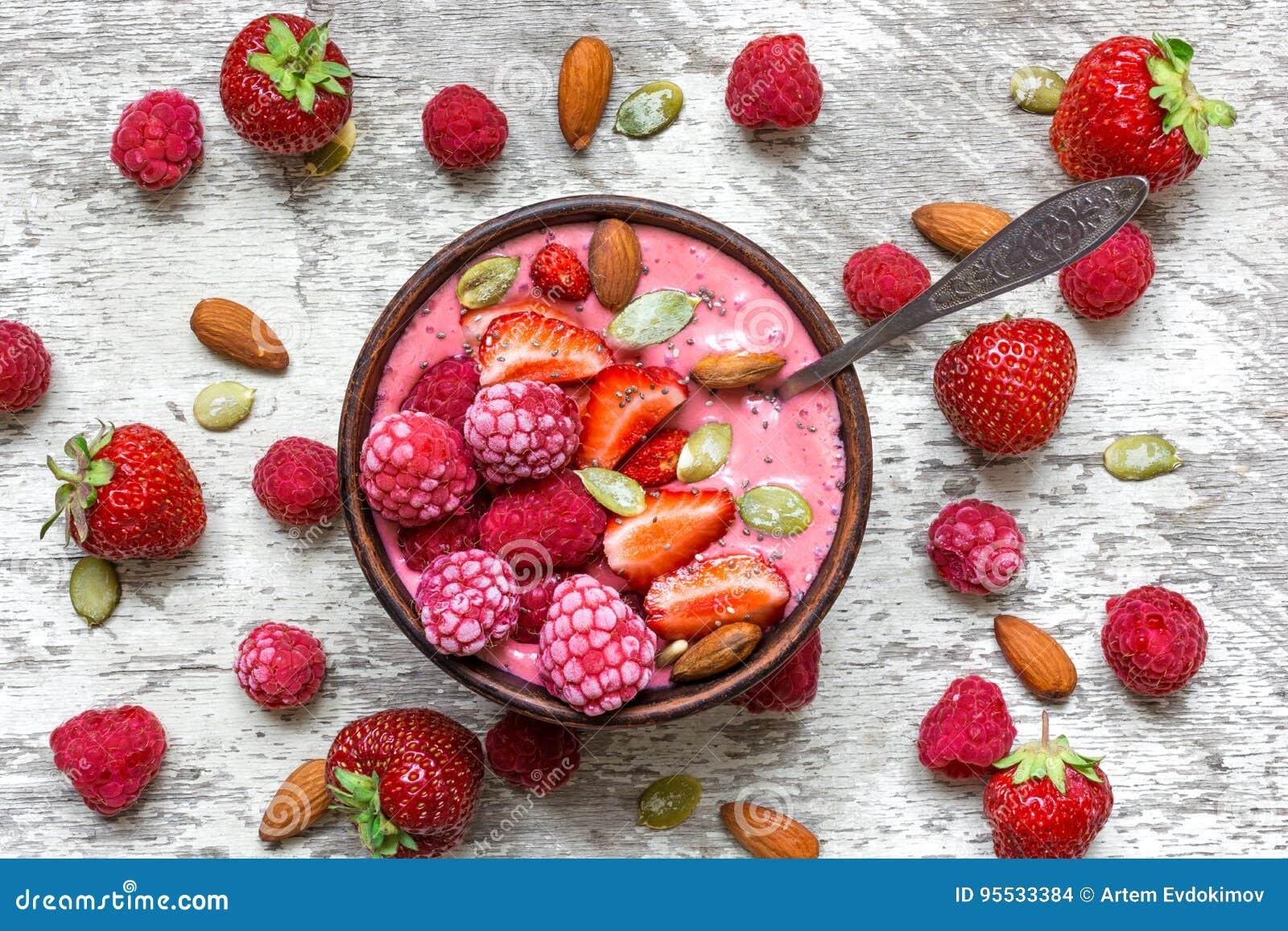 Roze frambozen en aardbeifruit smoothie of milkshake in een kom met bessen, noten en zaden