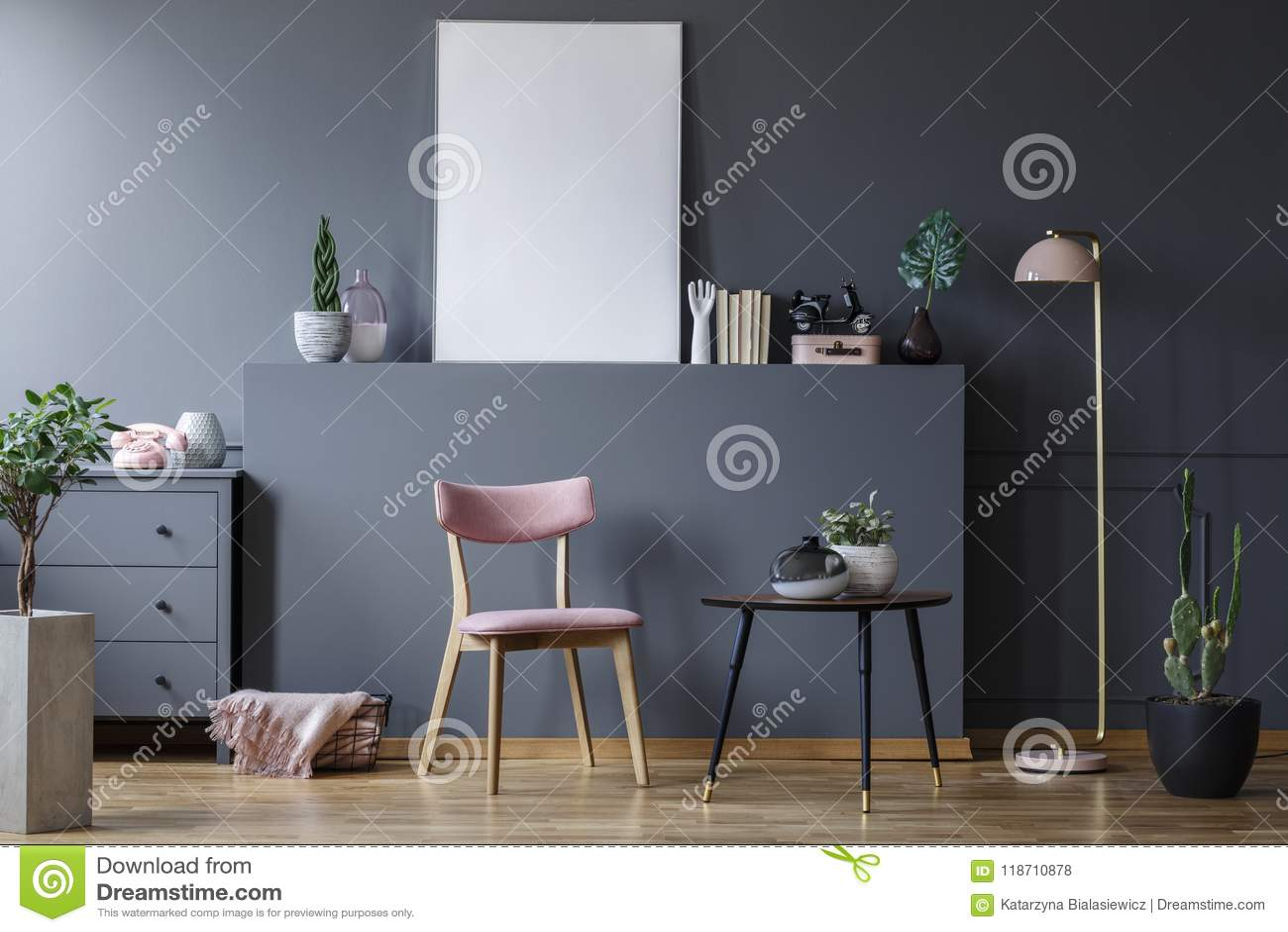 Roze houten stoel bij zwarte lijst in grijs woonkamerbinnenland
