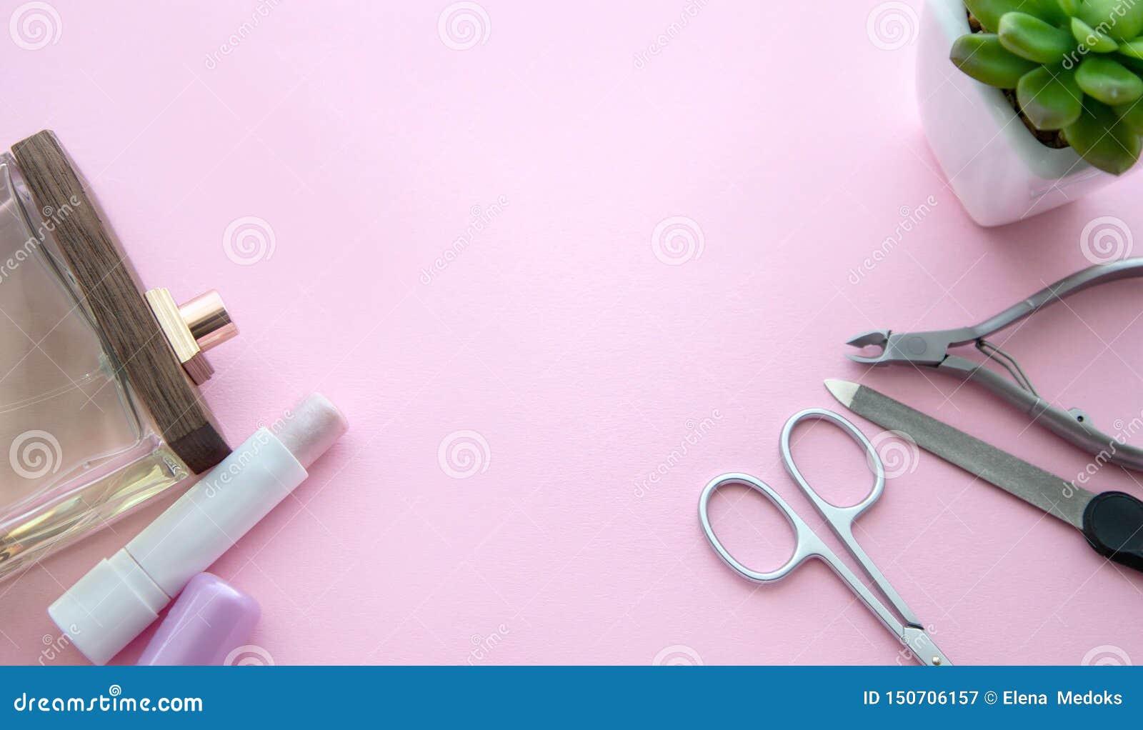 Roze lippenstift, parfumfles, manicureschaar, nagelvijl, opperhuidtangen en groene bloem in een witte pot op een roze achtergrond