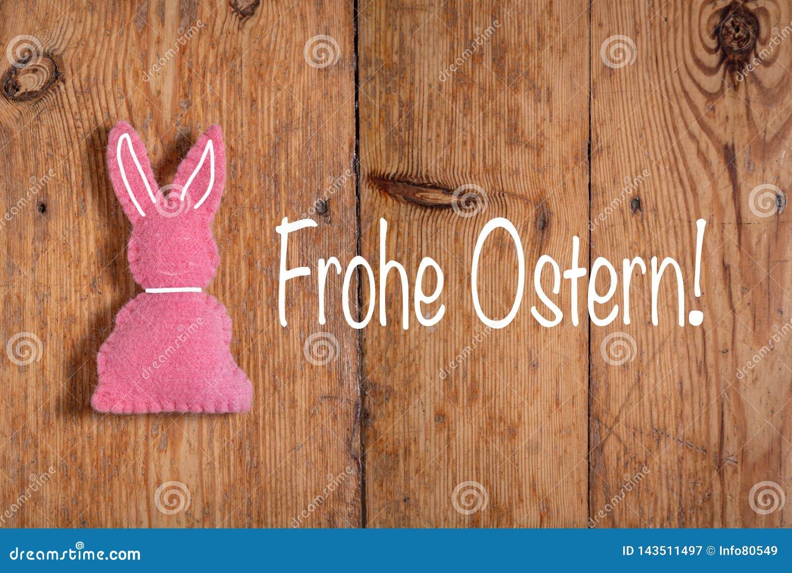 Roze Paashaas met tekst 'Frohe Ostern 'en een houten achtergrond Vertaling: 'Gelukkige Pasen '