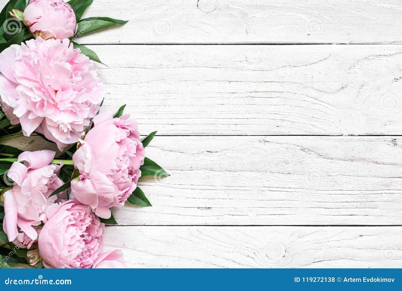 Roze pioenbloemen over witte houten lijst met exemplaarruimte De uitnodiging van het huwelijk Vlak leg